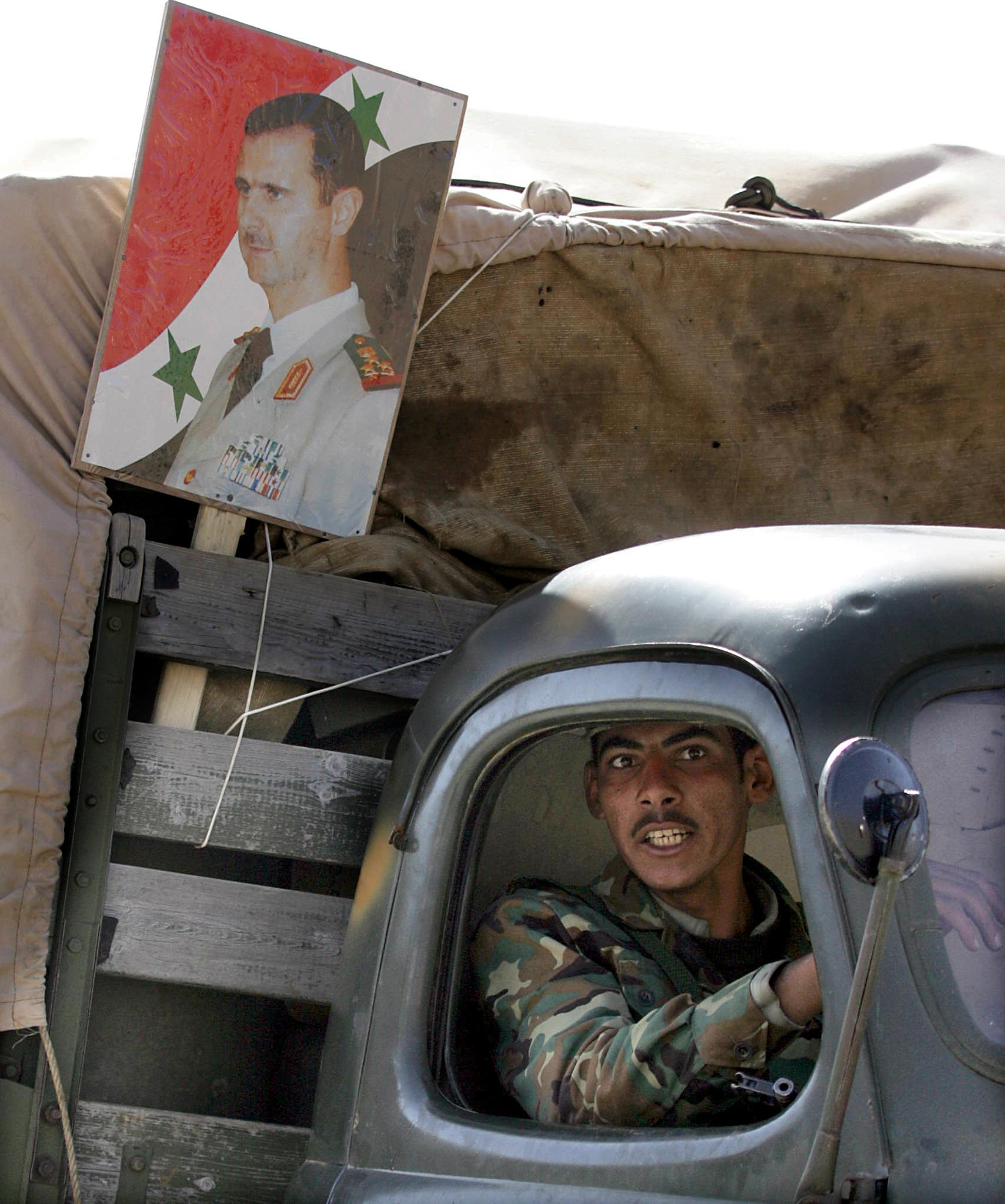 A Syrian soldier sits in a truck, decora