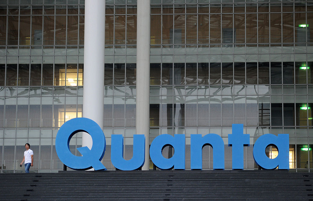 A man walks past a Quanta logo outside t