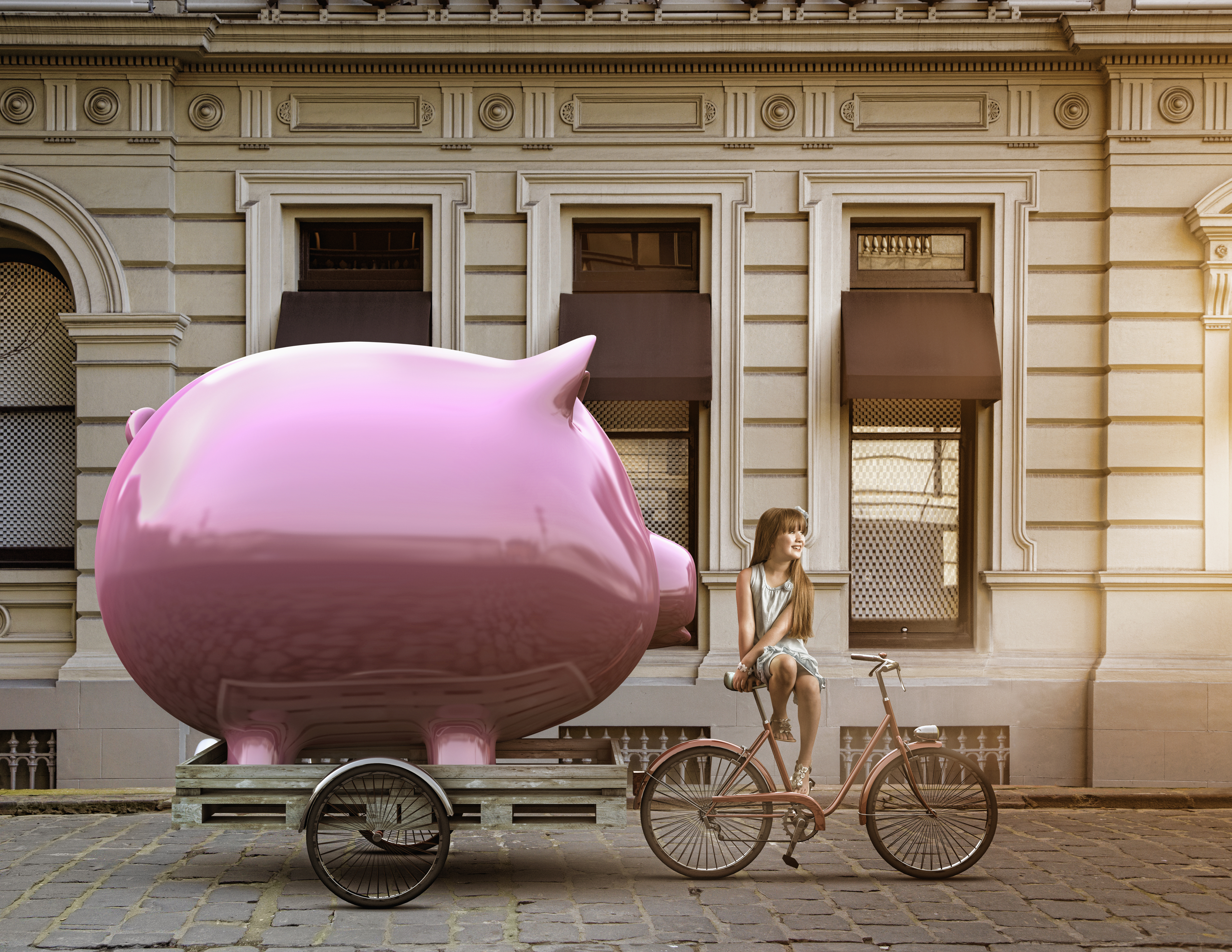 Girl pulling piggy bank on bicycle cart