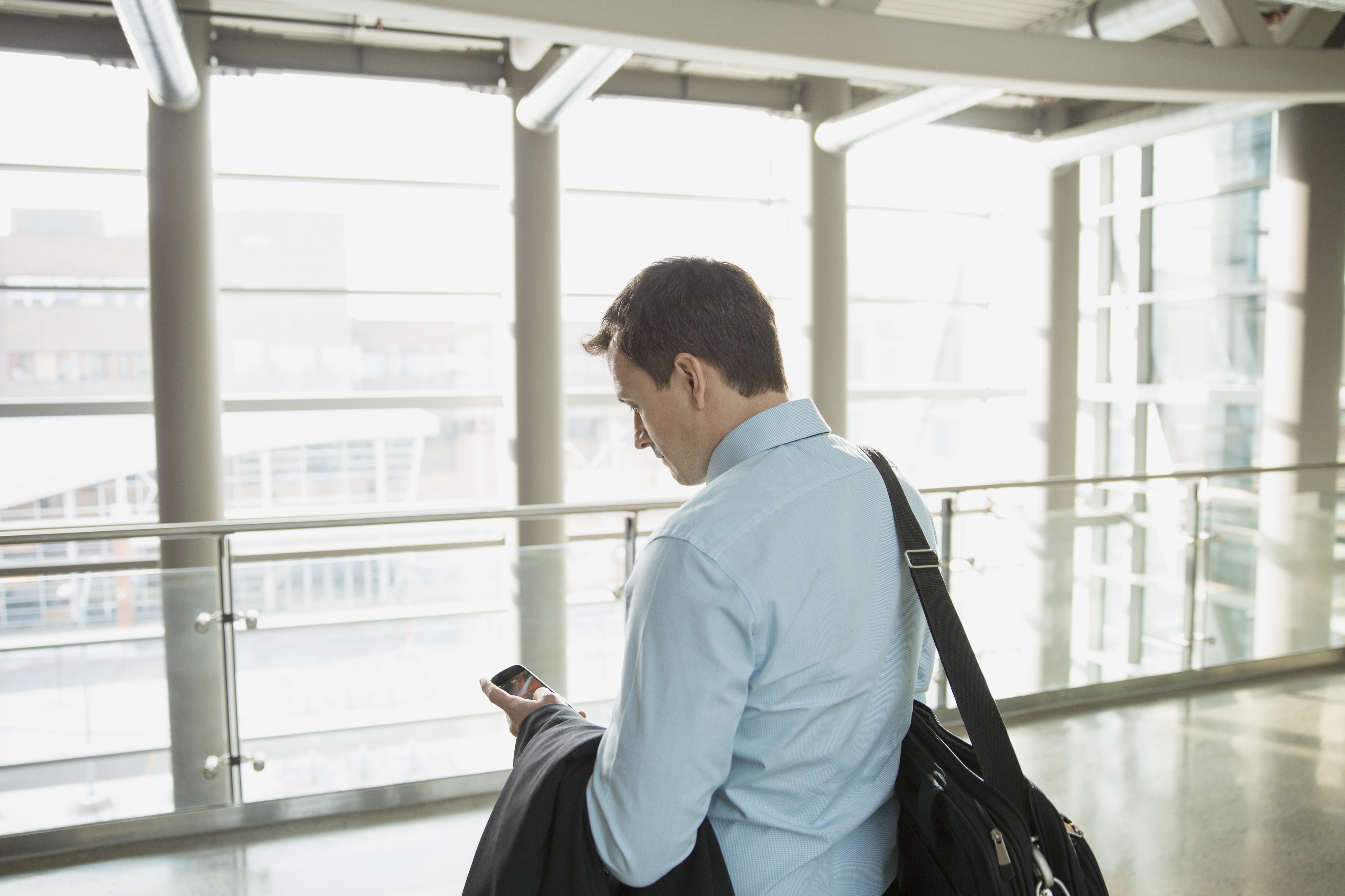 Businessman holding briefcase and texting with smart phone