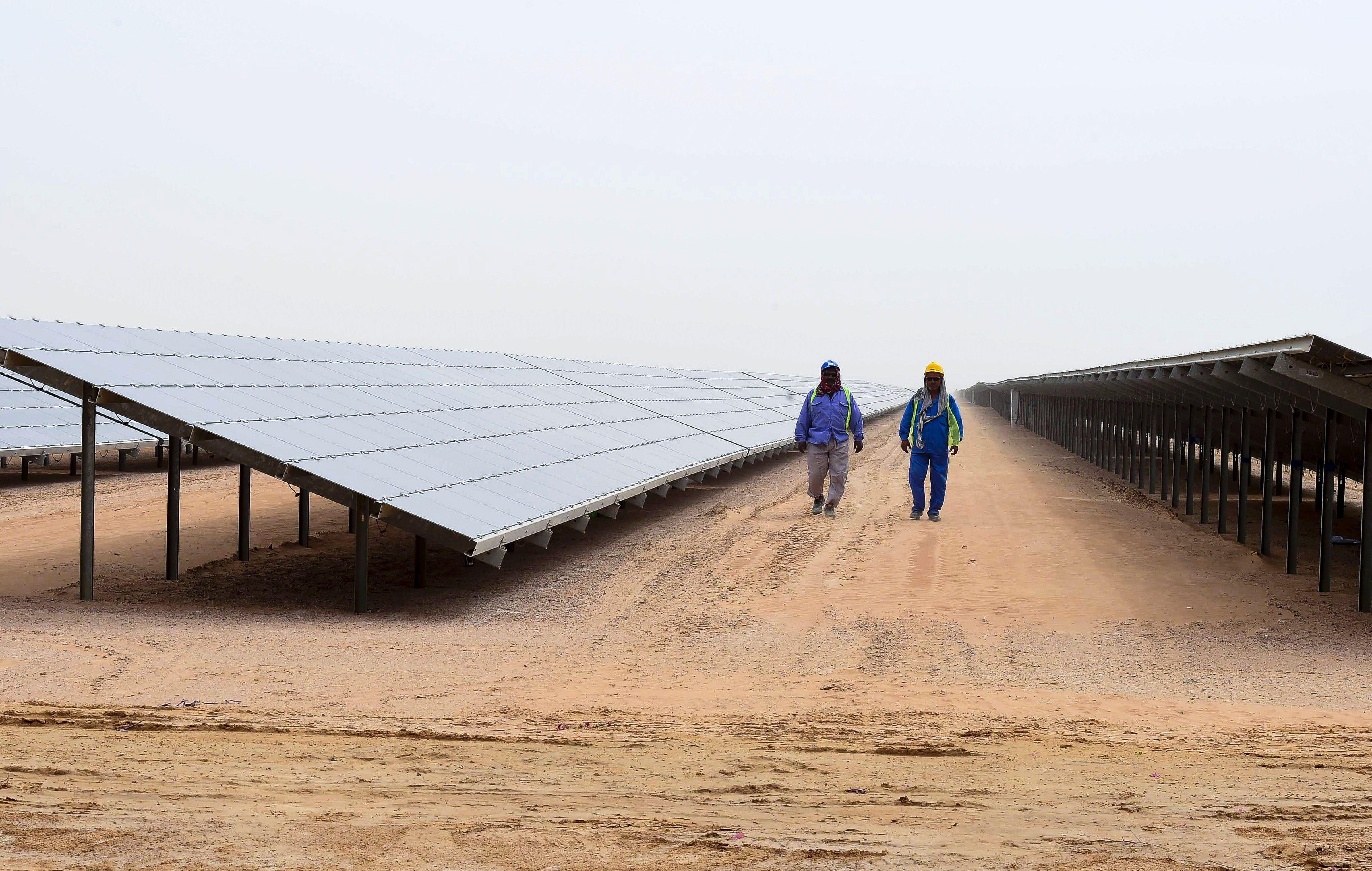 Employees walk past solar panels at the Mohammed bin Rashid Al-Maktoum Solar Park on March 20, 2017, in Dubai.