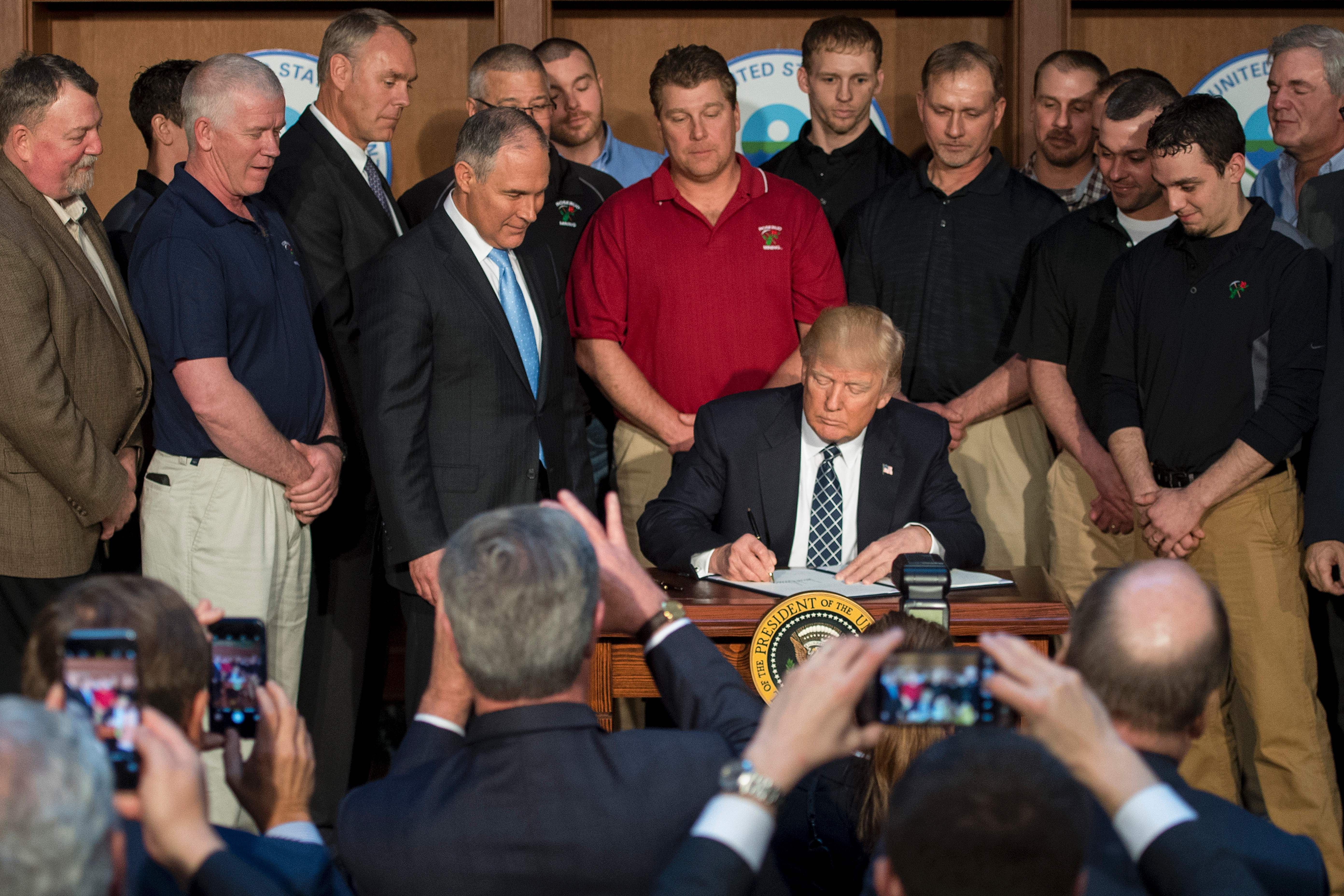 Surrounded by miners from Rosebud Mining, U.S. President Donald Trump signs the Energy Independence Executive Order at the Environmental Protection Agency (EPA) Headquarters in Washington, DC, March 28, 2017.