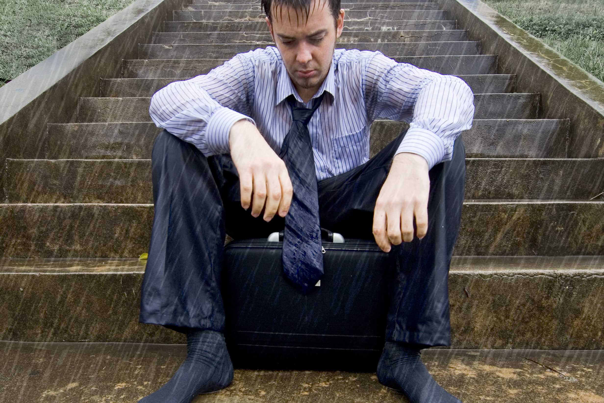 A businessman sits in the pouring rain