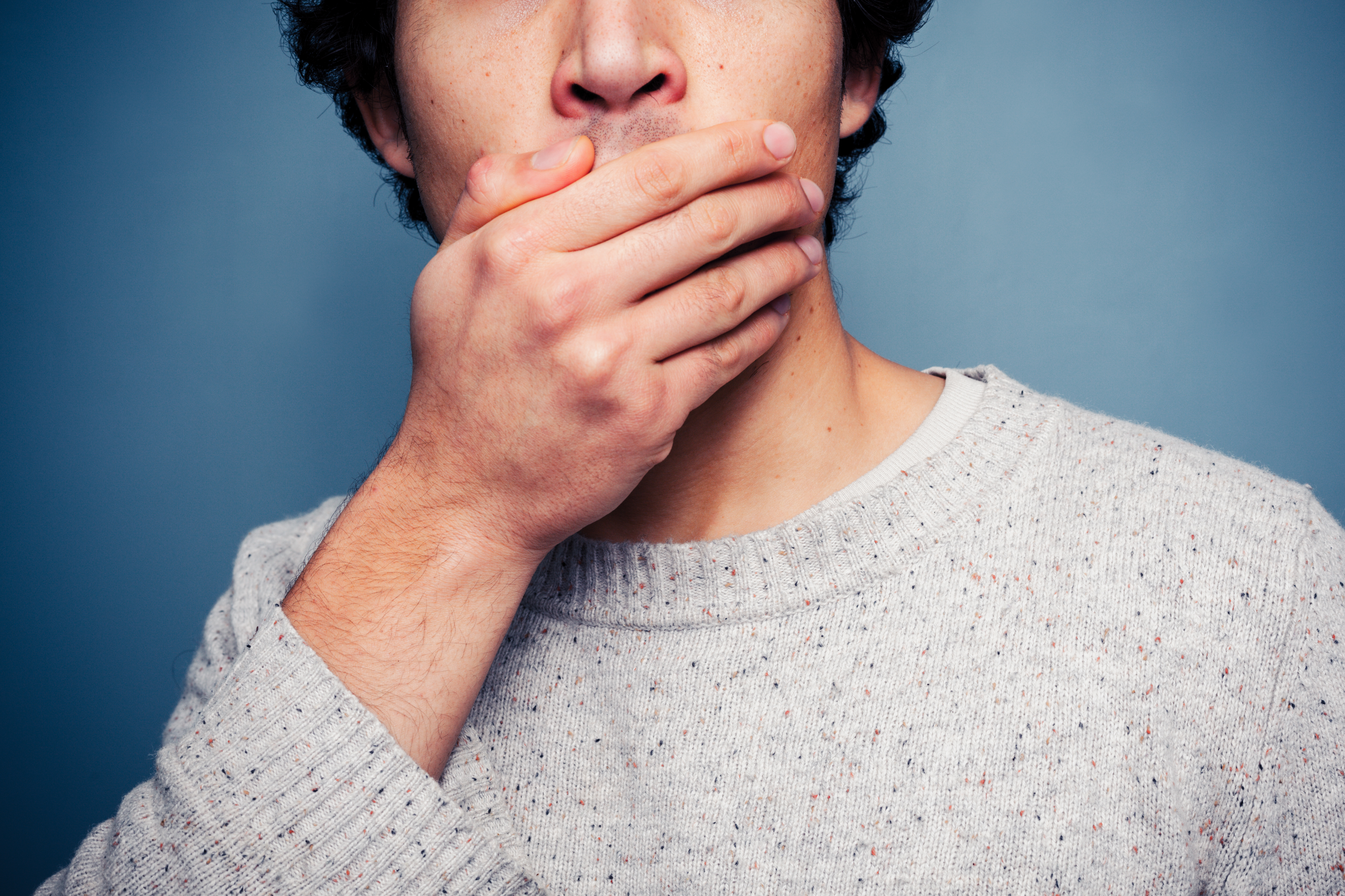 Shocked young man covering his mouth