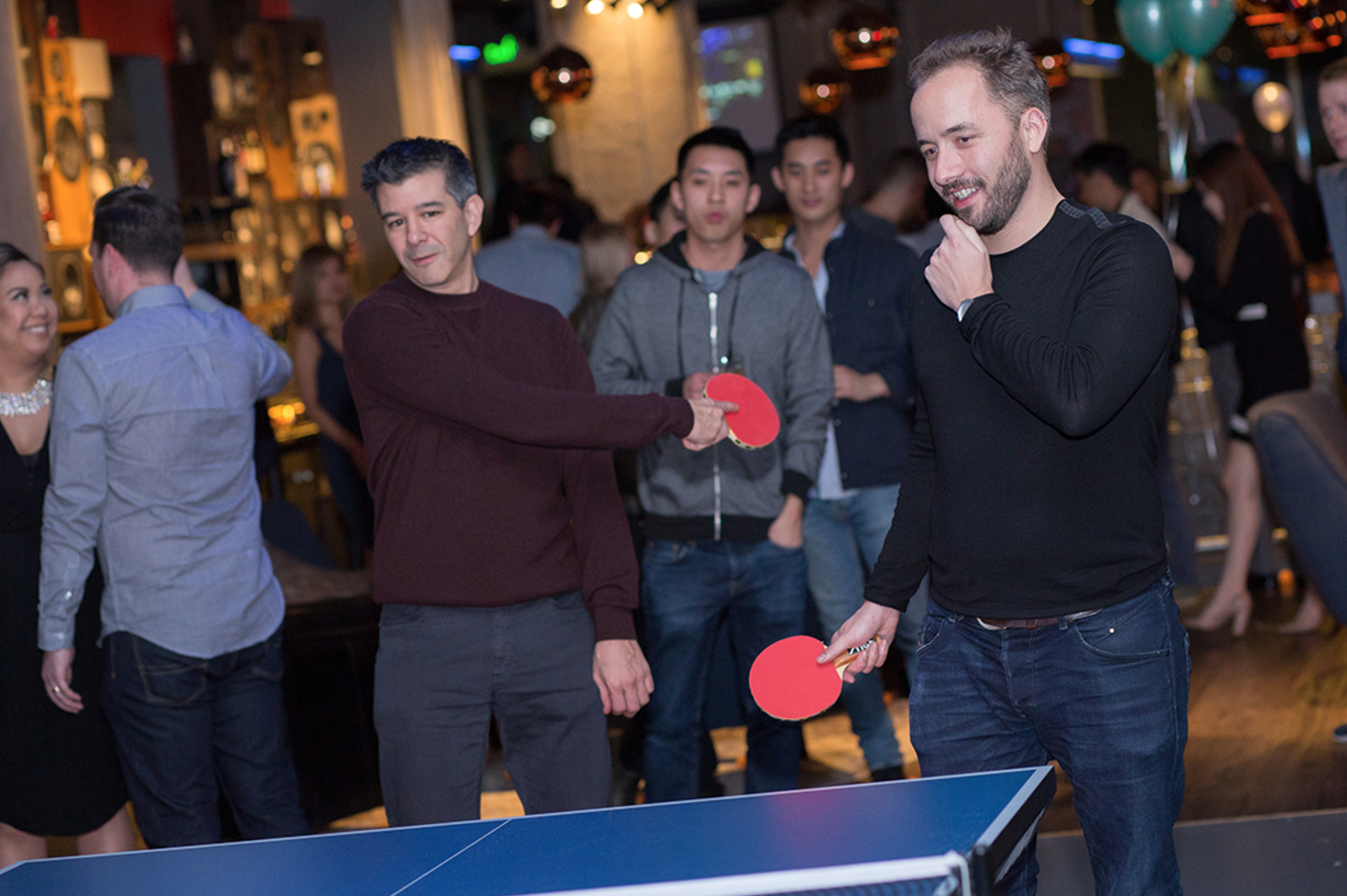 "Uber CEO Travis Kalanick plays ping pong with Drew Houston at ""Babes and Balls"" event."