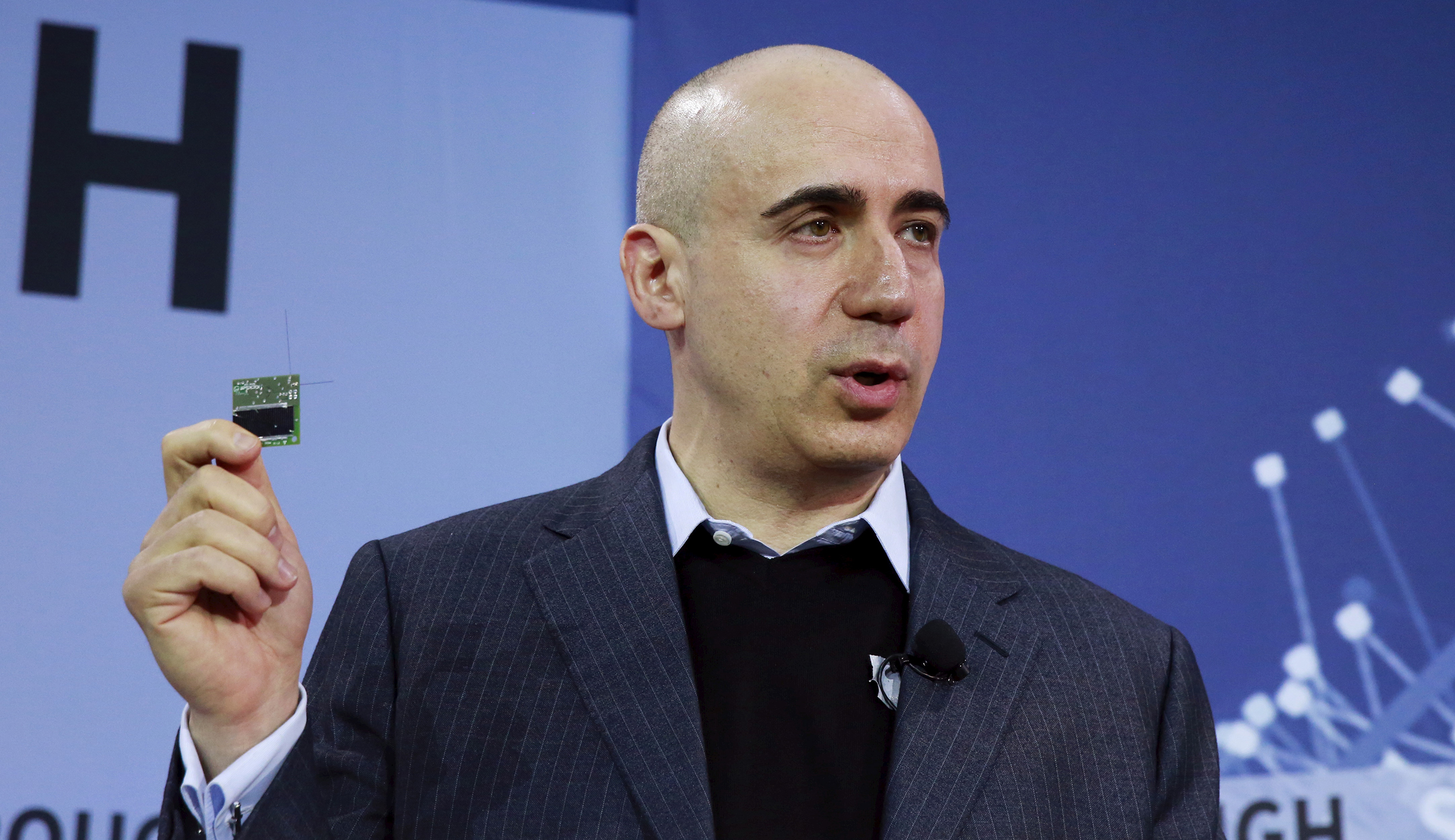 Investor Yuri Milner holds a small chip during an announcement of the Breakthrough Starshot initiative in New York