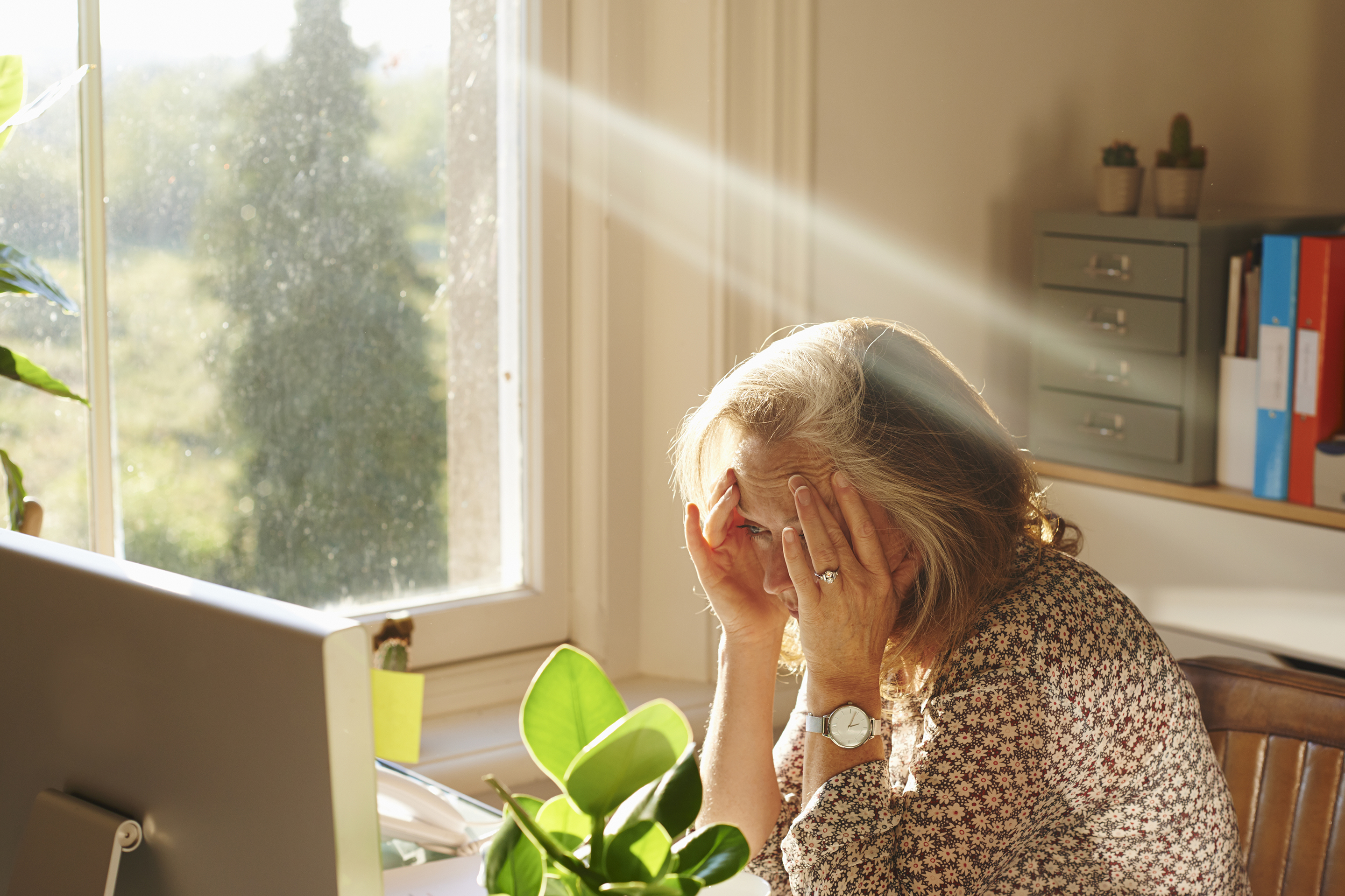 Stressed woman using computer in sunny home office
