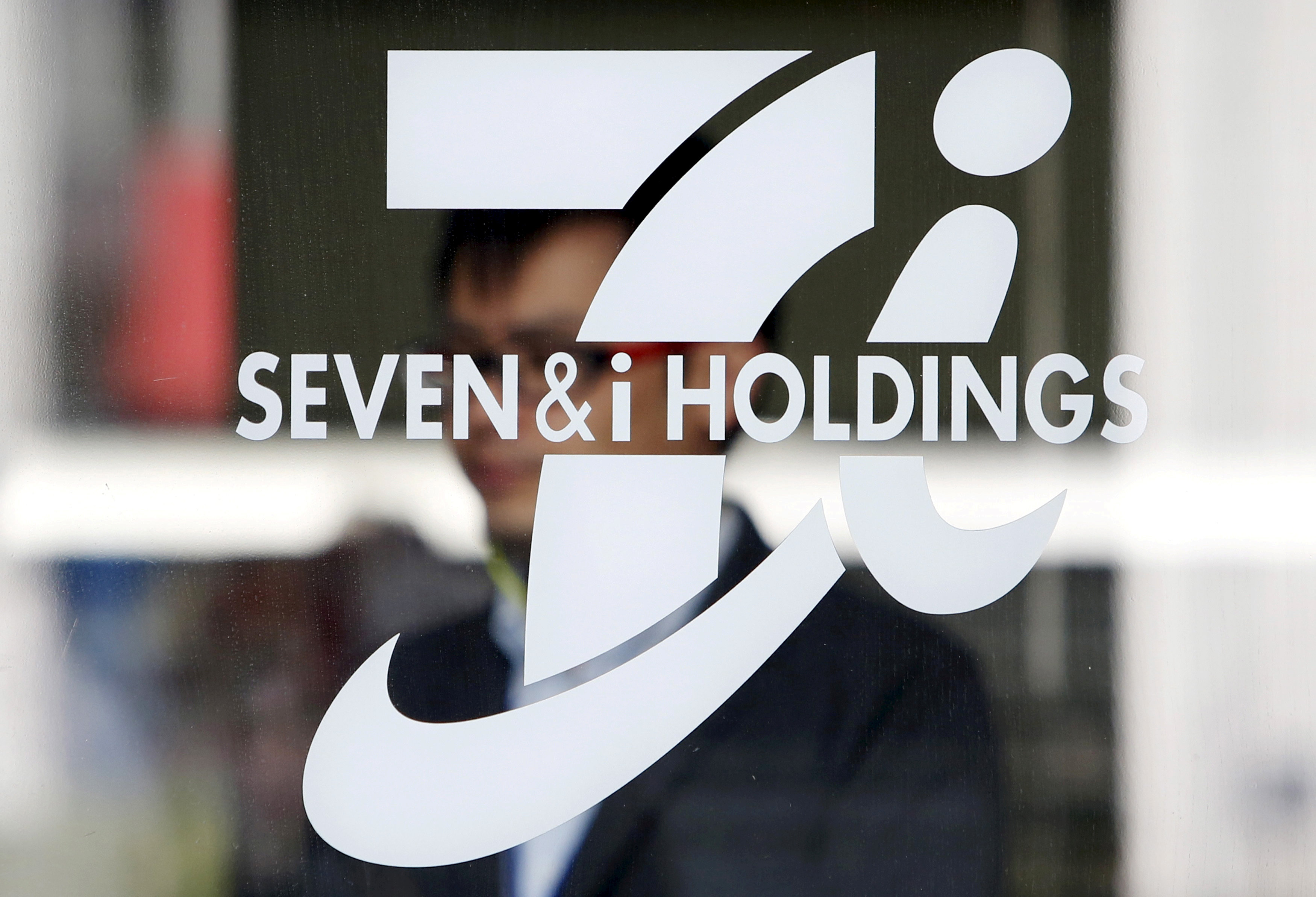 FILE PHOTO: A shopper is seen behind a Seven & I Holdings' logo at a 7-Eleven convenience store in Tokyo