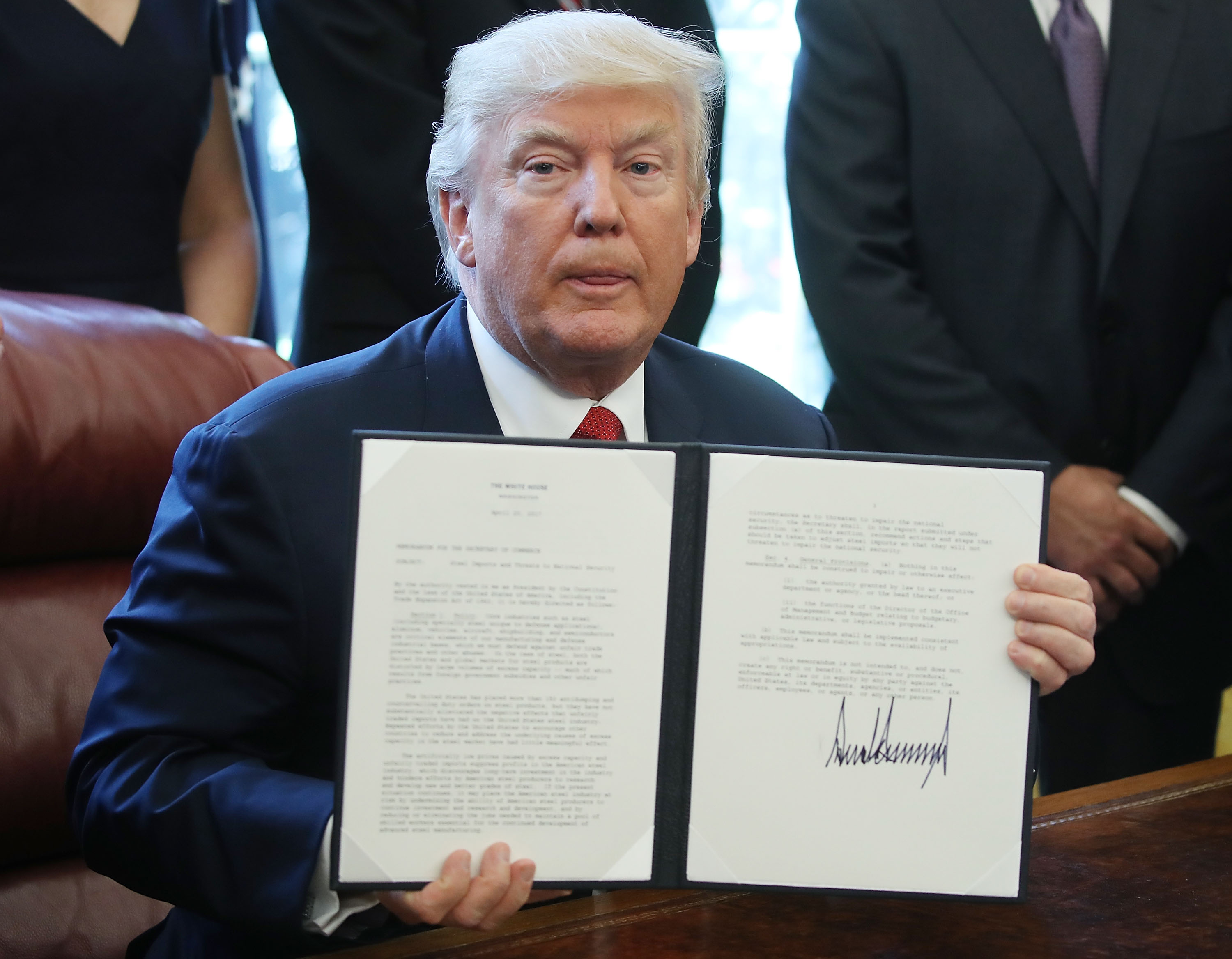 President Trump holds up an Executive Memorandum on the investigation of steel imports, after signing it in the Oval Office at the White House, on April 20.