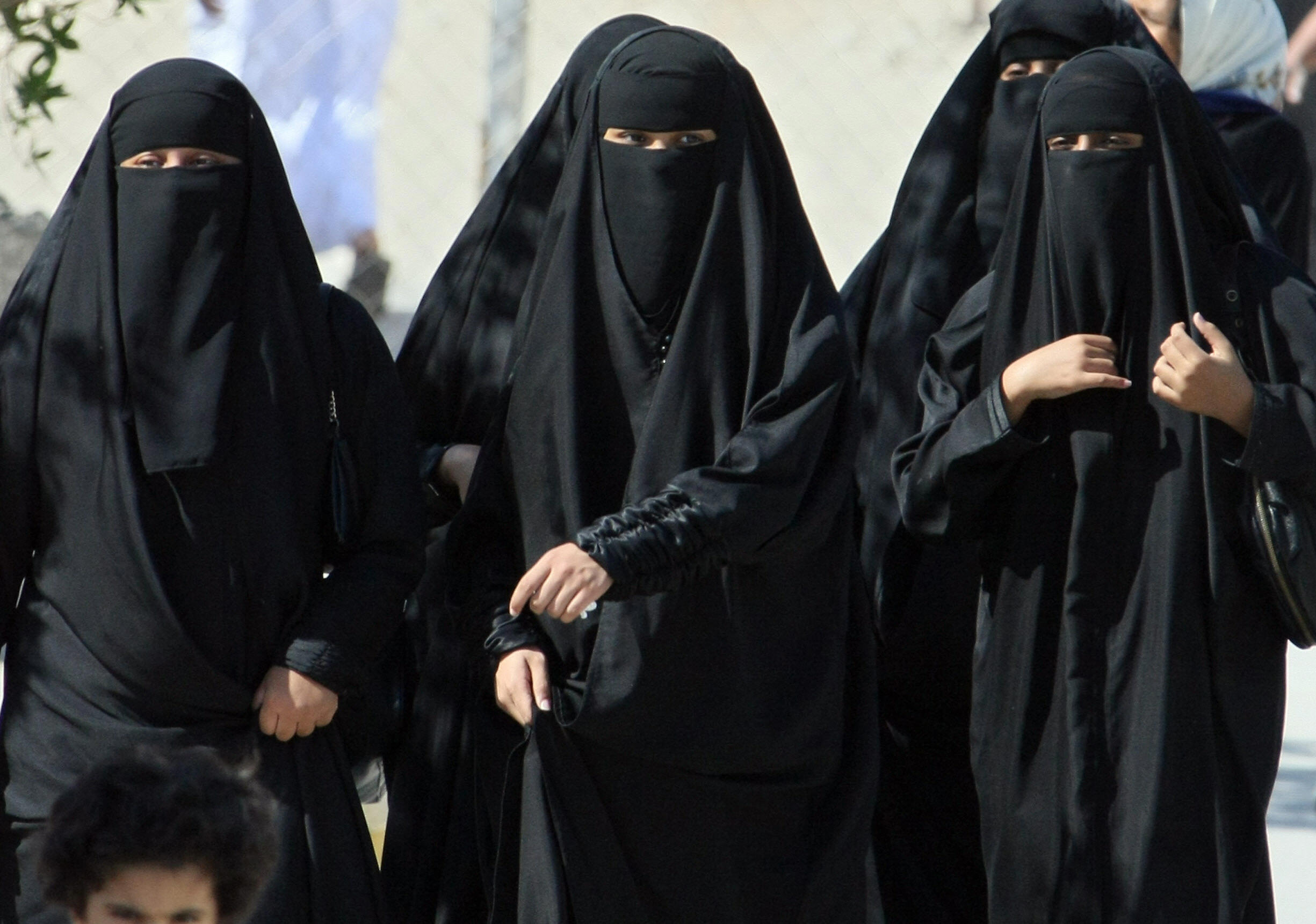 Saudi women cross a street in Hofuf city