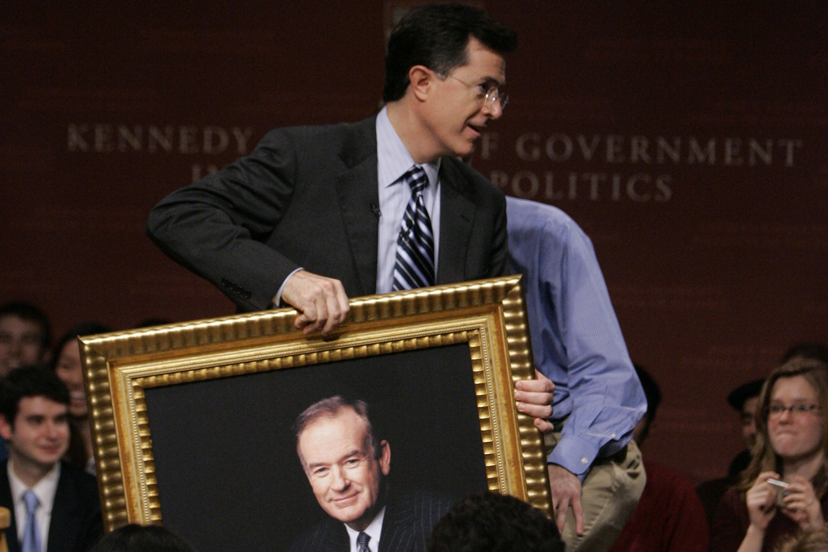 Comedian Stephen Colbert carries a portrait of radio talk show host Bill O'Reilly while addressing a gathering at Harvard University's John F. Kennedy School of Government in Cambridge, Mass. on Dec. 1, 2006.