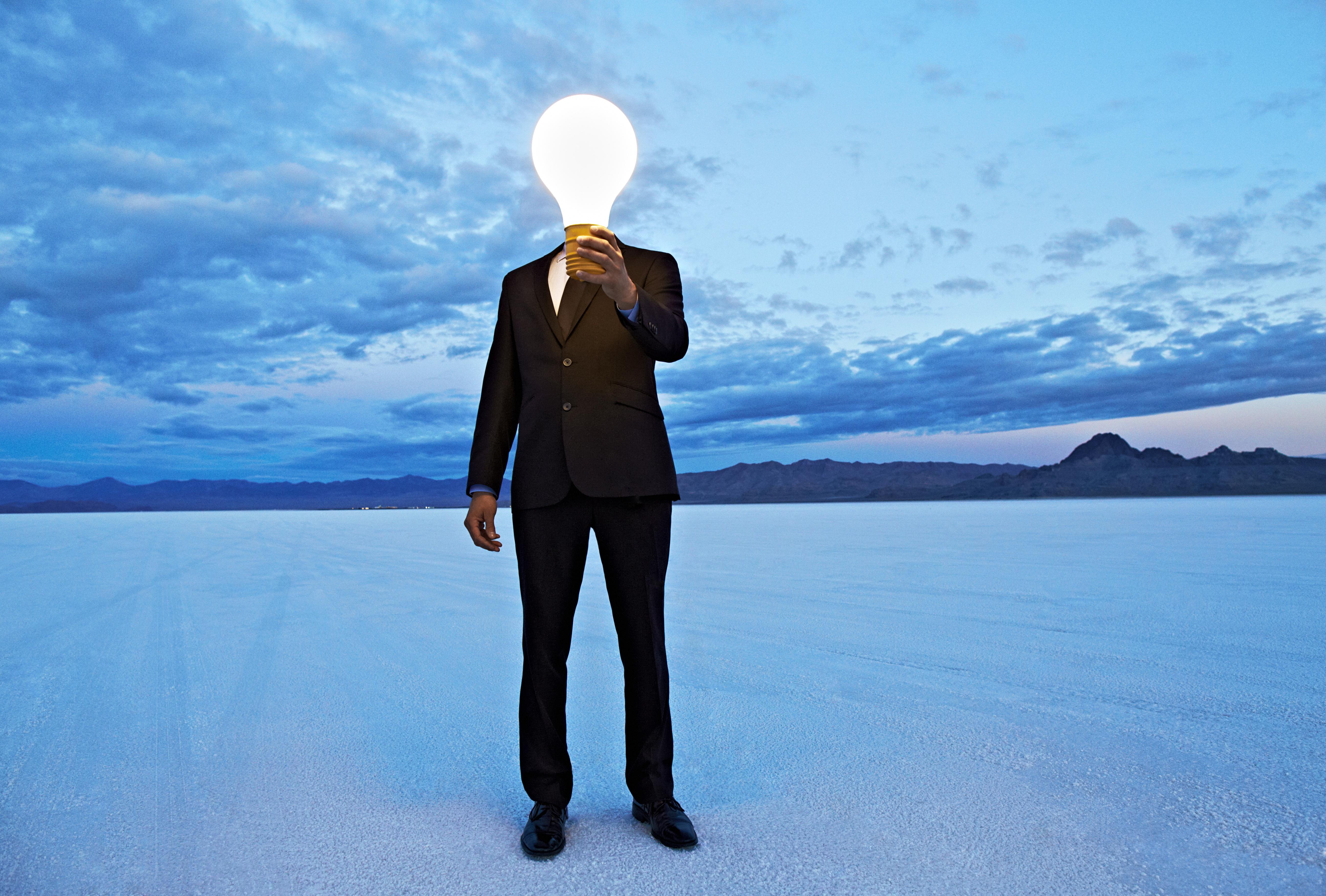 Man holding giant lightbulb in front of head.