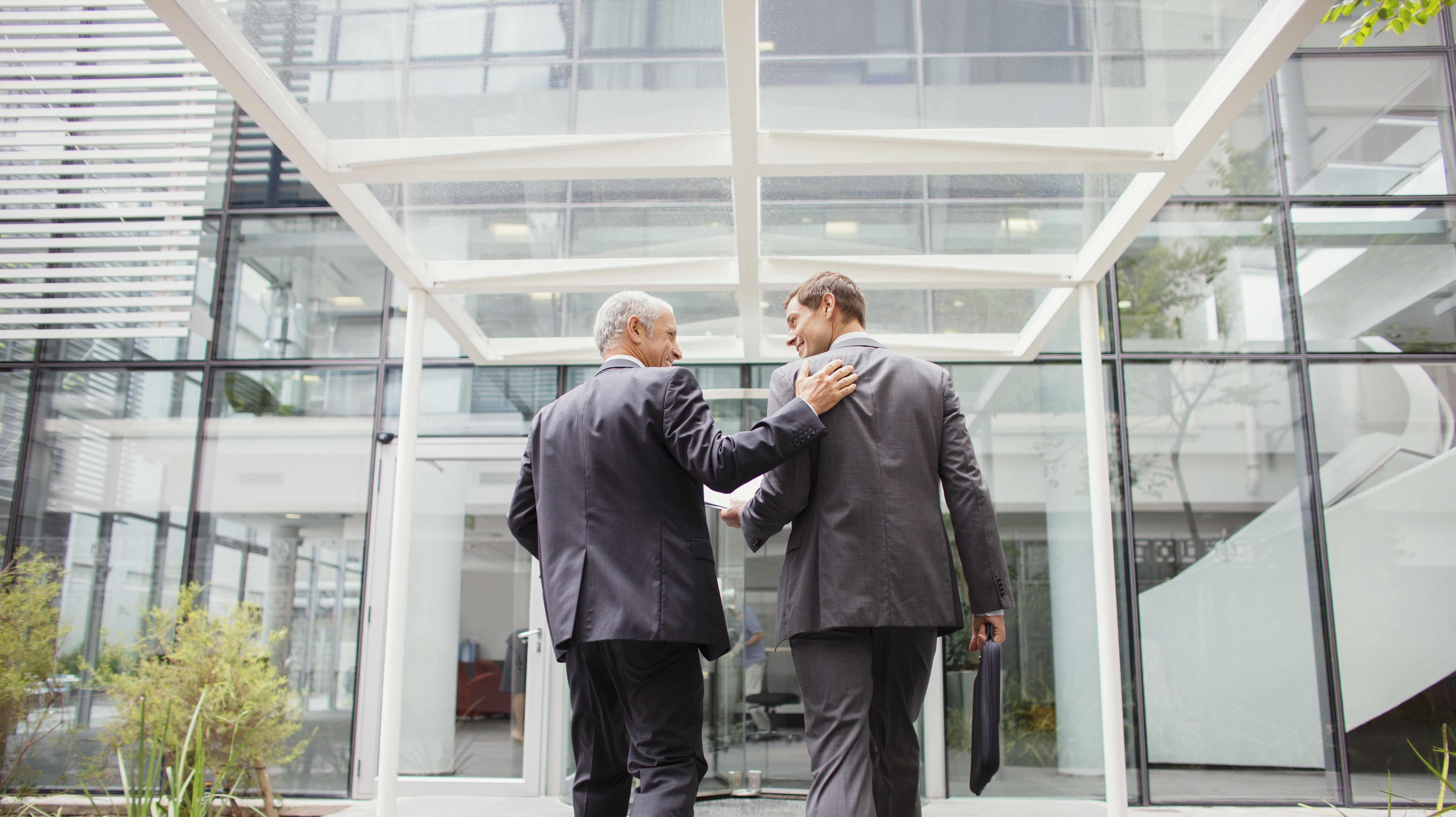 Businessmen walking into office building together