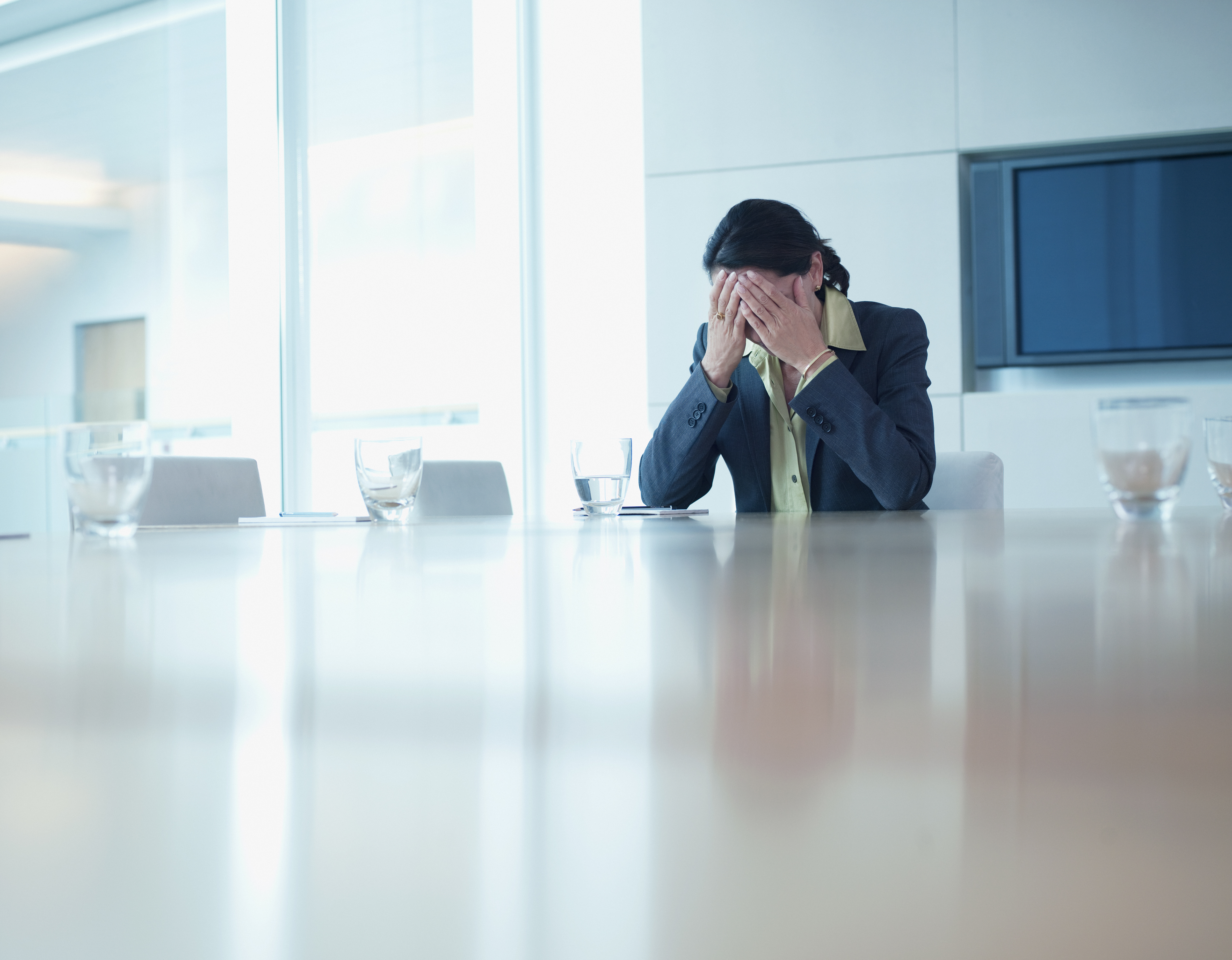 Sad businesswoman sitting at conference table