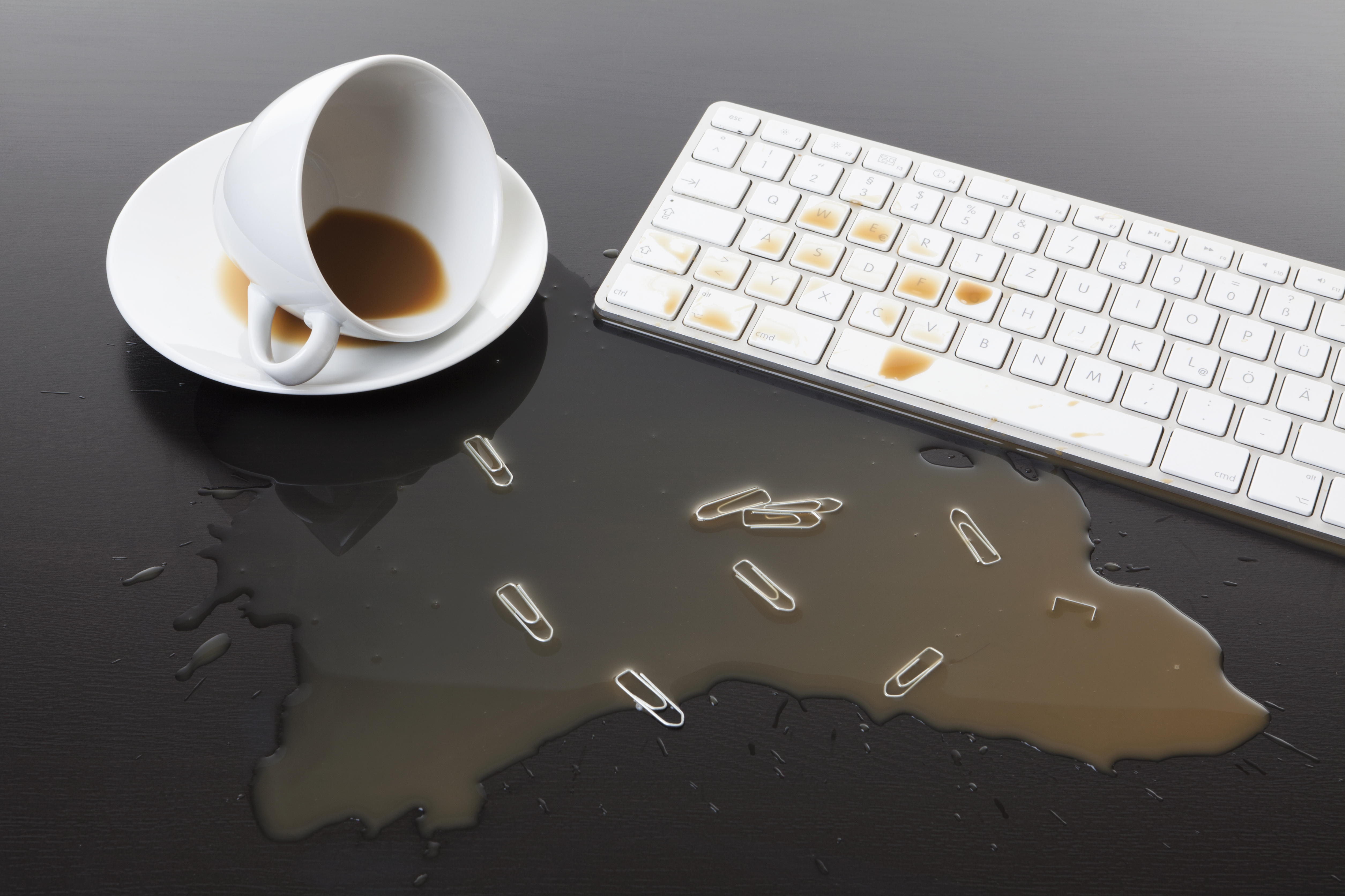 A cup of coffee spilled on a computer keyboard