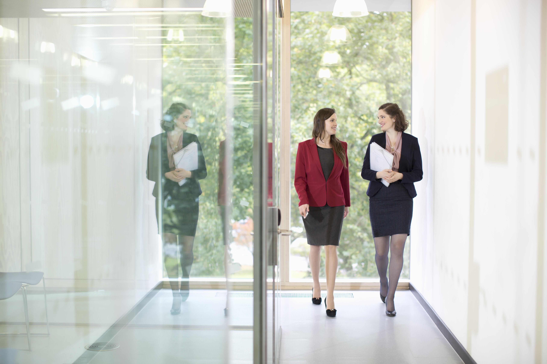 Businesswomen walking in modern office hallway