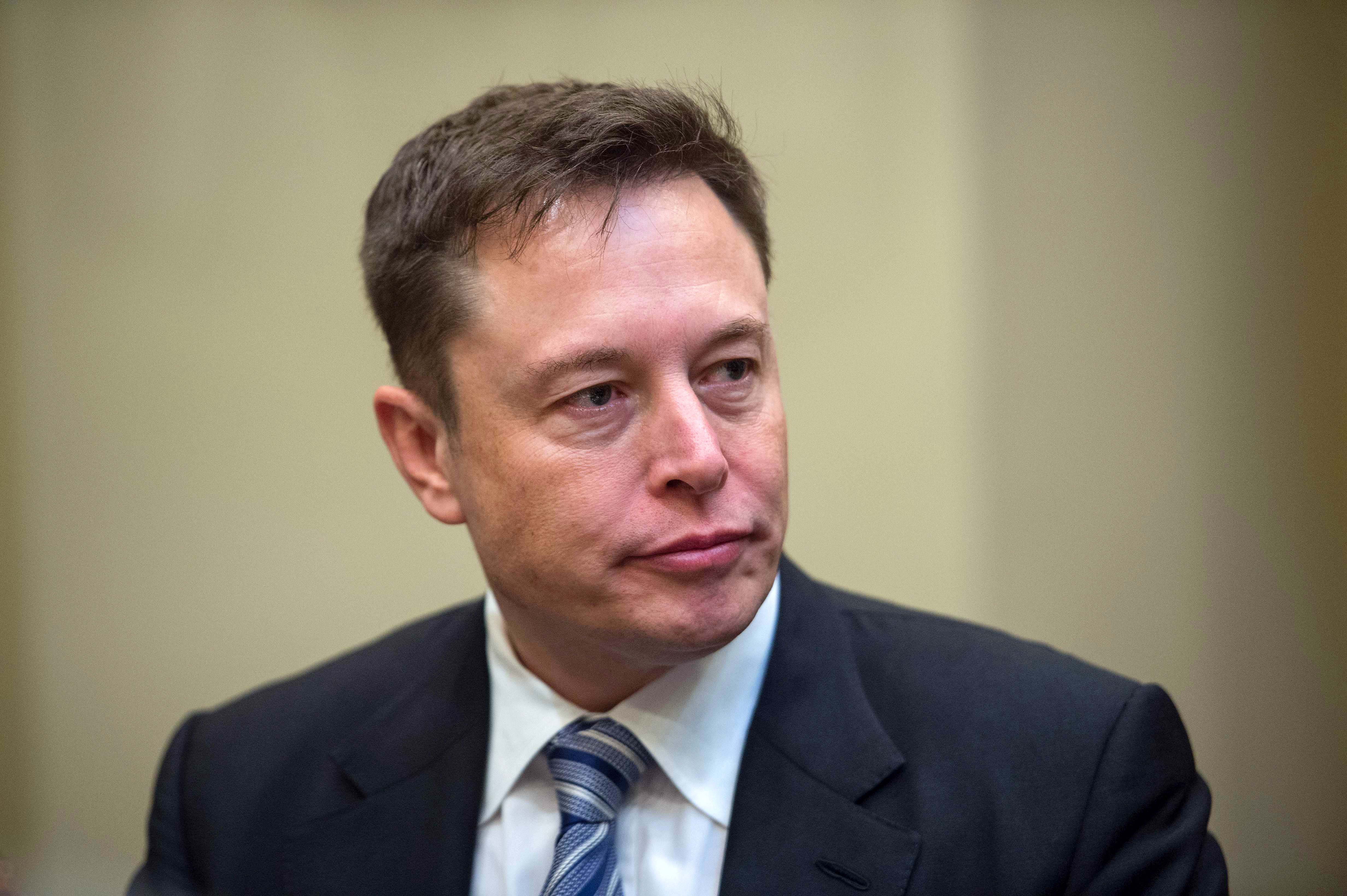 Elon Musk listens to President Donald Trump speak during a meeting with business leaders in the Roosevelt Room at the White House in Washington, DC, on January 23, 2017.