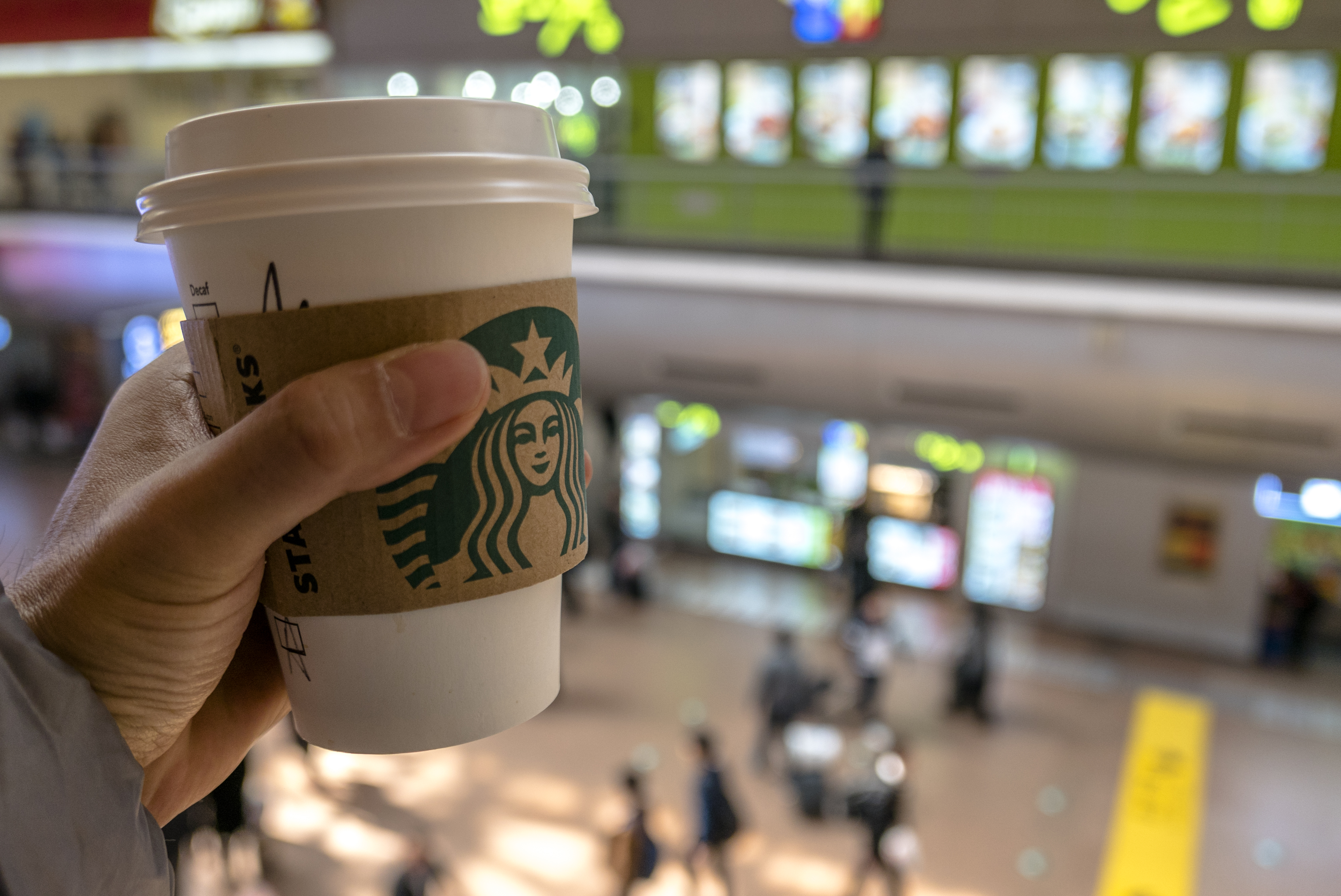 Hand holding a Starbucks coffee cup in a shopping area.