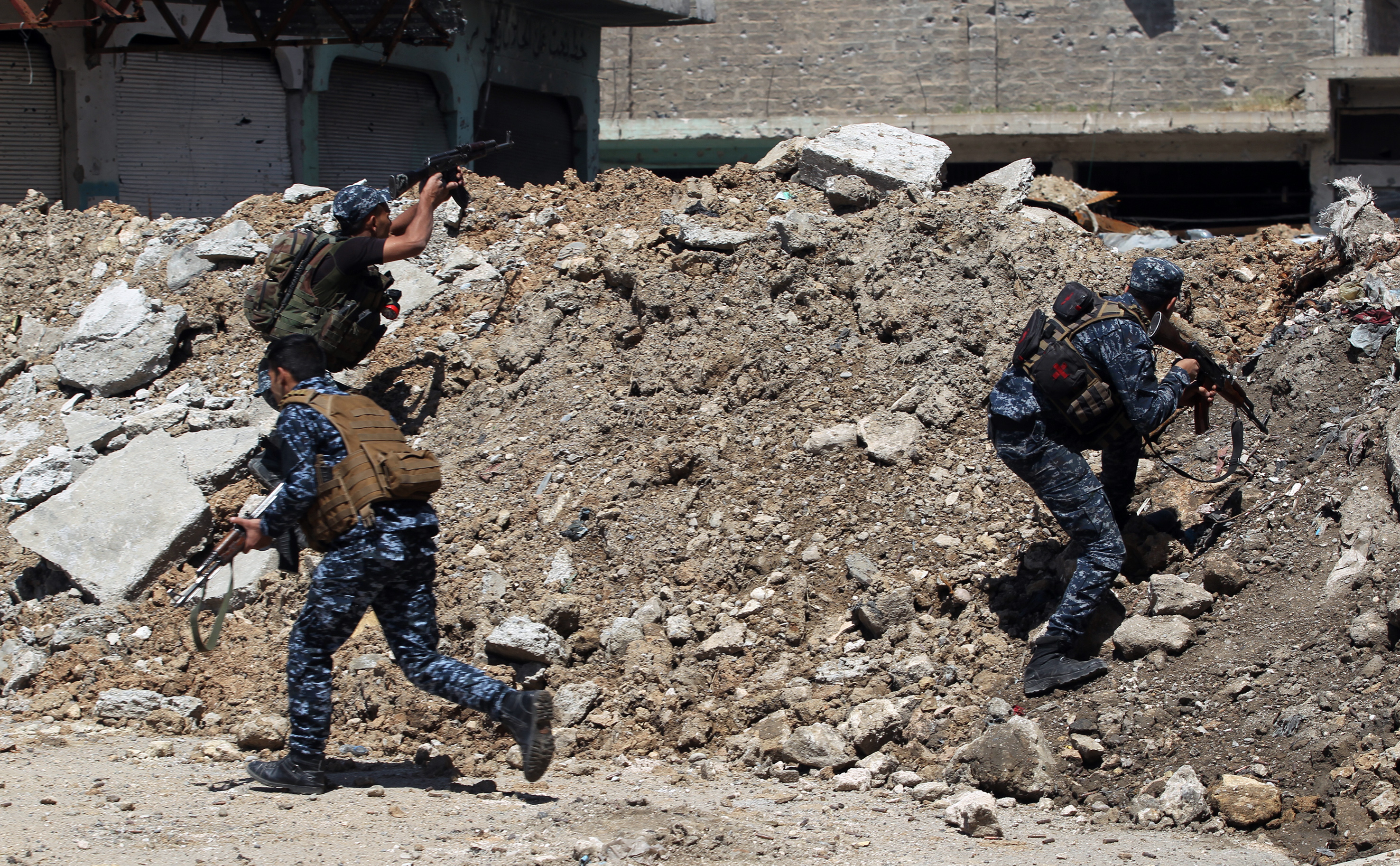 Members of the Iraqi military shoot suppressive fire while taking cover behind a barrier made of debris in the old city of Mosul during the offensive to recapture the city from ISIS fighters, on April 16, 2017.