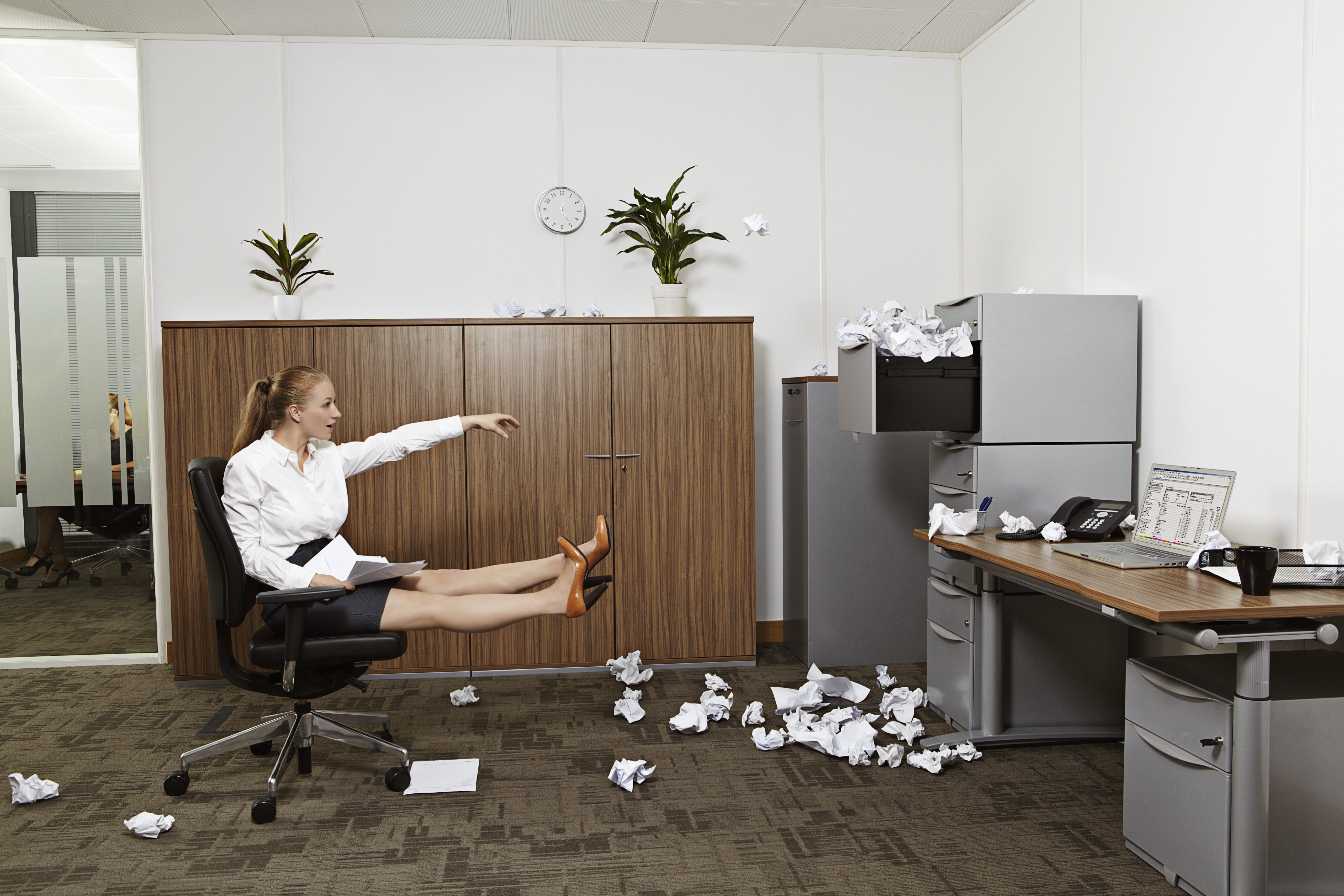 Businesswoman throwing crumpled paper into file cabinet