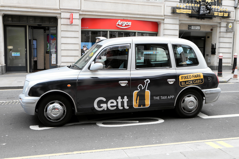 "Gett app  ""fixed fare""  advert advertisement on black taxi cab in street Cheapside, London UK  KATHY DEWITT"