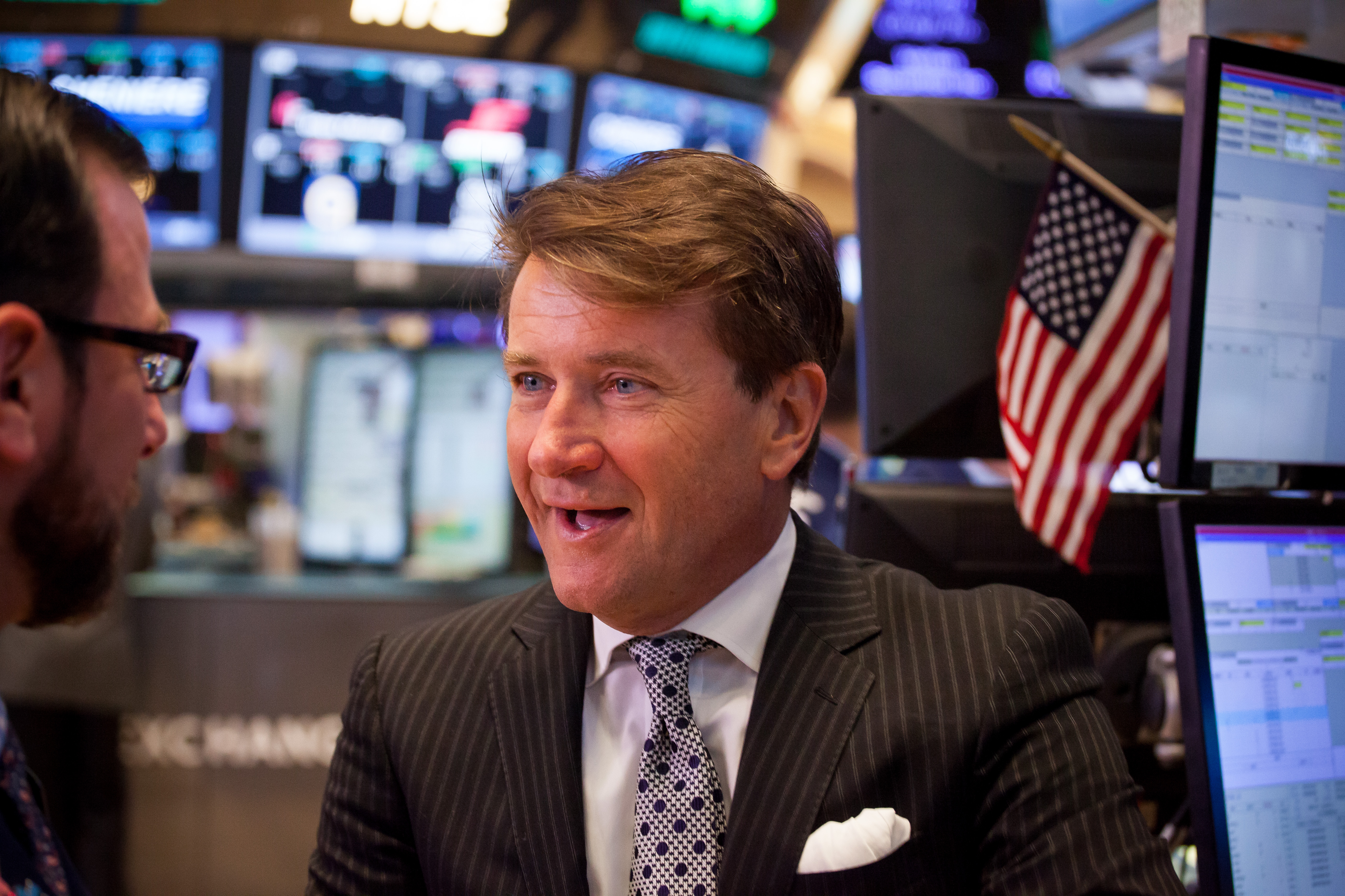Robert Herjavec, founder and chief executive officer of the Herjavec Group, right, talks with a trader on the floor of the New York Stock Exchange (NYSE) in New York, U.S., on Friday, Jan. 13, 2017.