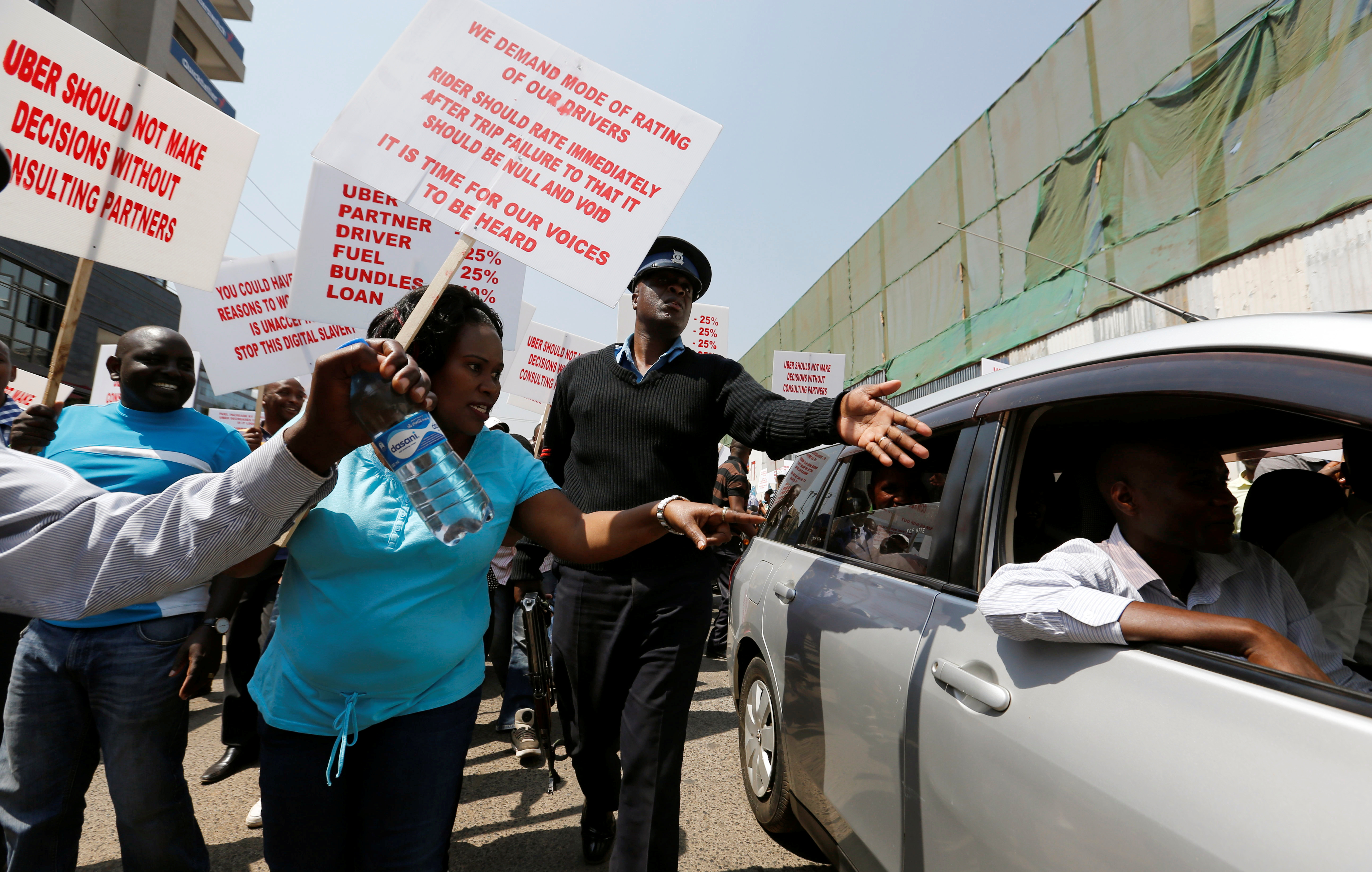 A policeman intervenes as Kenyan taxi drivers signed up to ride-hailing service Uber attempt to eject a passenger from an Uber operating taxis during a strike in Nairobi