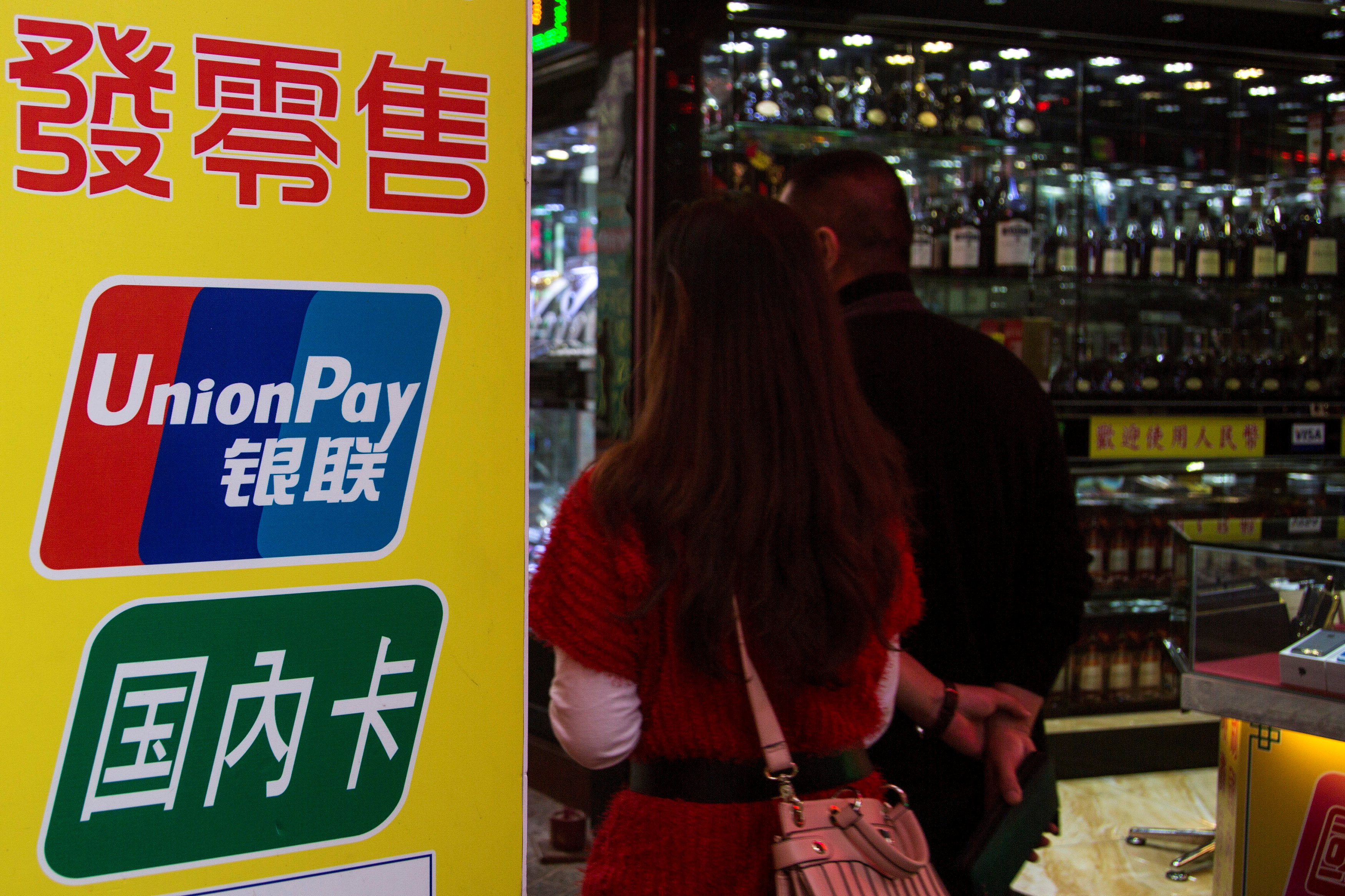 FILE PHOTO - Chinese visitors walk past a sign for China UnionPay outside a pawnshop in Macau