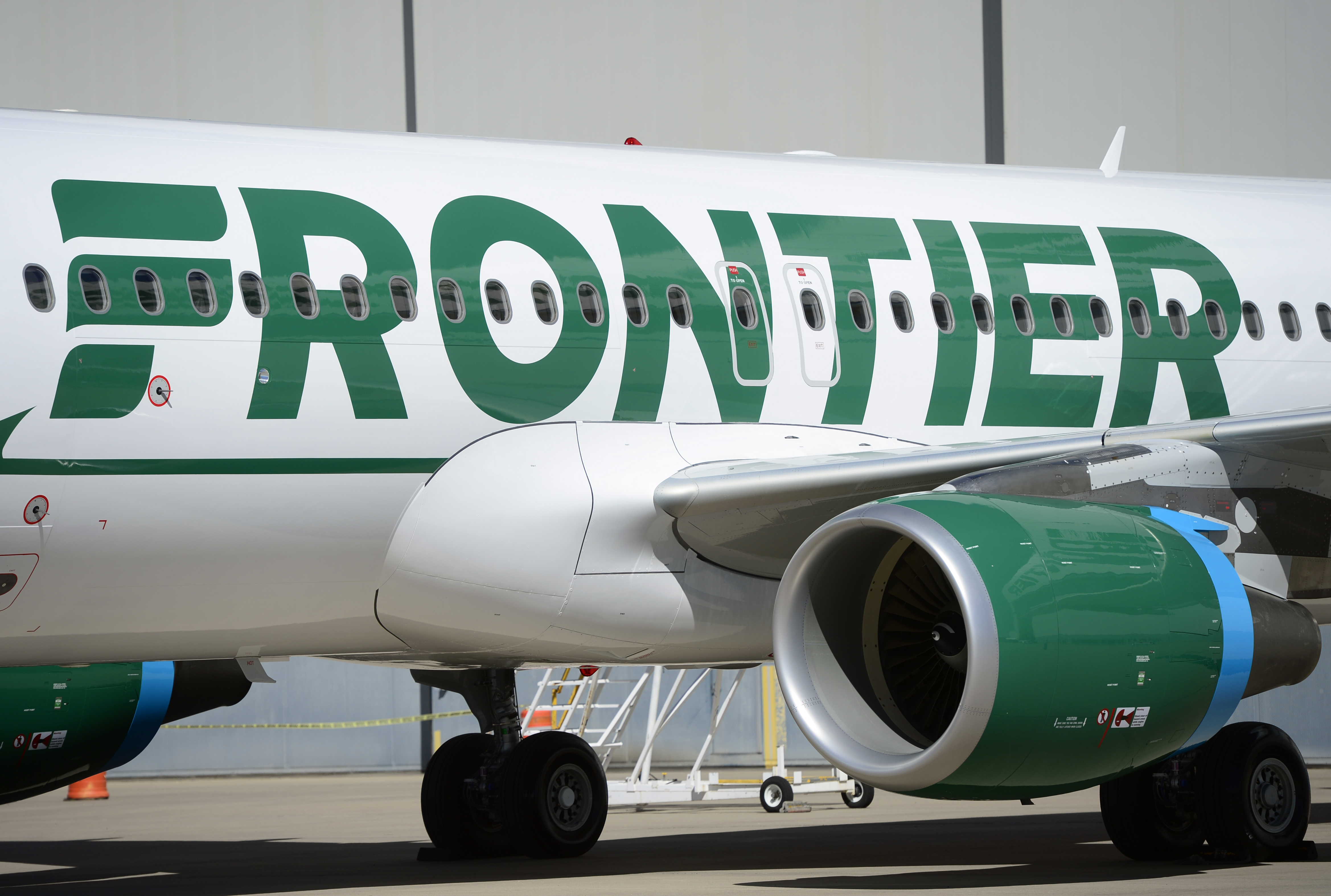 Frontier employees and executives physically pull a 46-ton Airbus A320 out of the Frontier Airlines hanger at Denver International Airport in Denver.