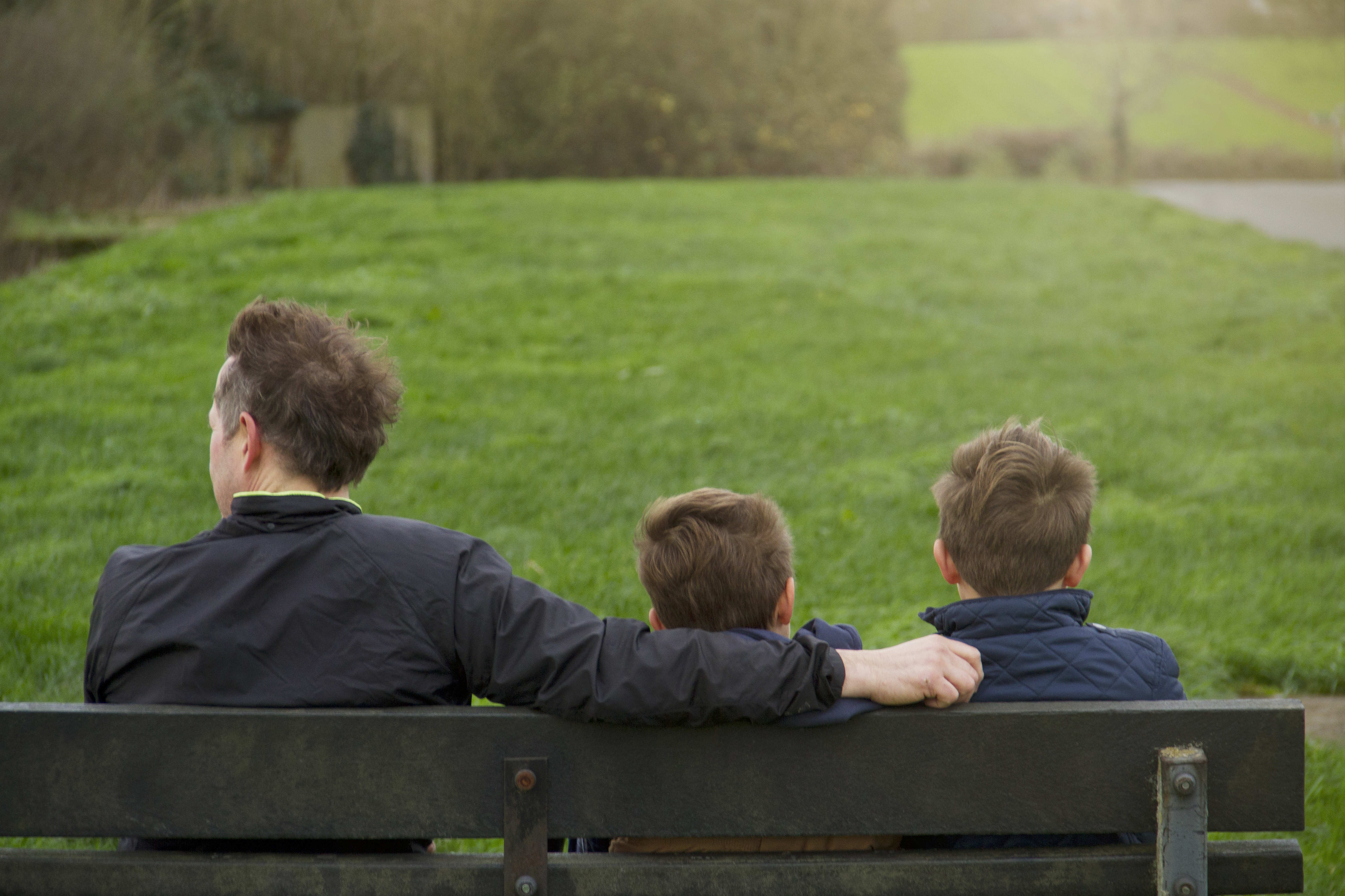 Father And Two Sons Sat On Bench In Countryside