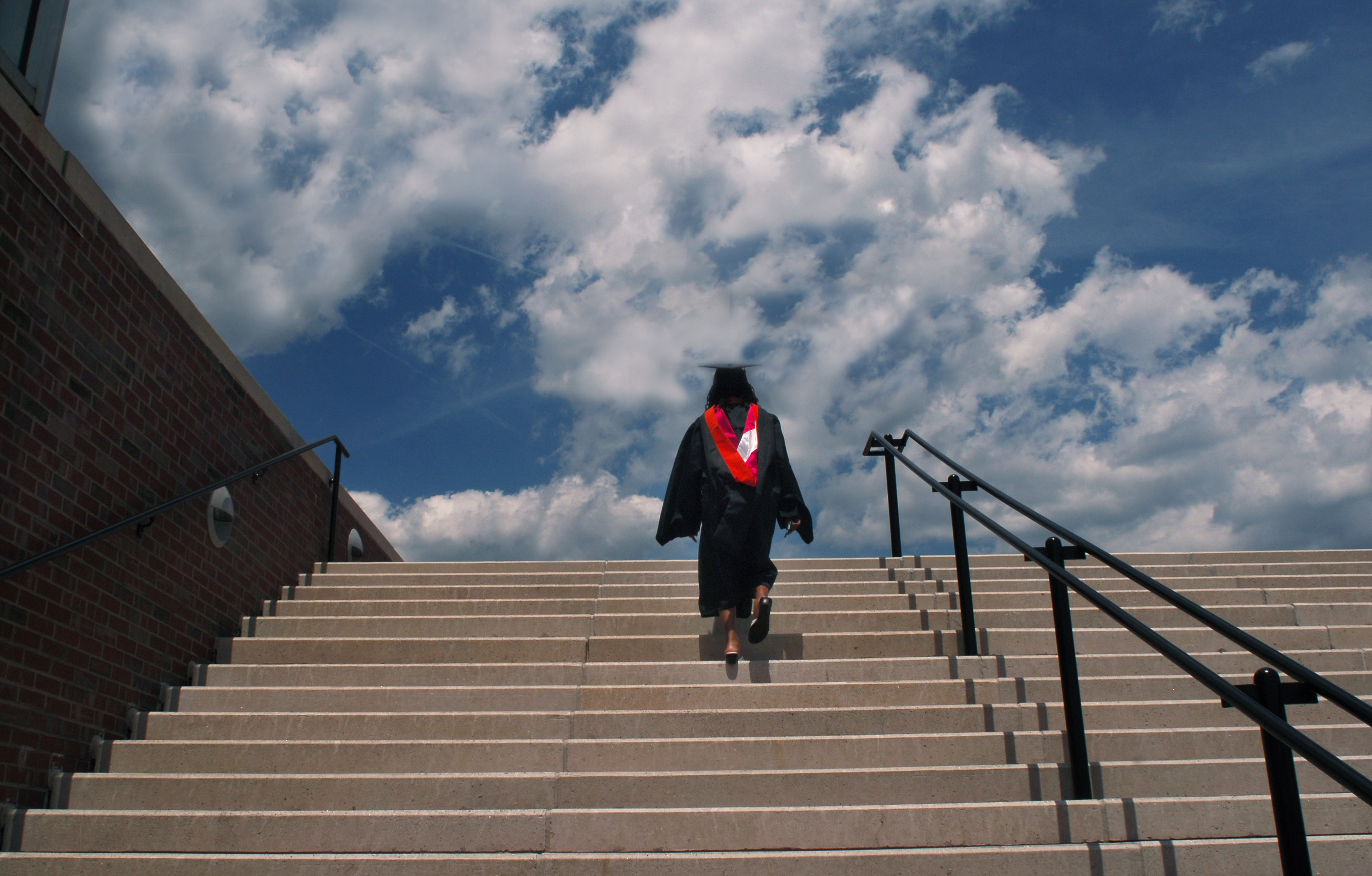 Woman walking up stairs to receive her degree