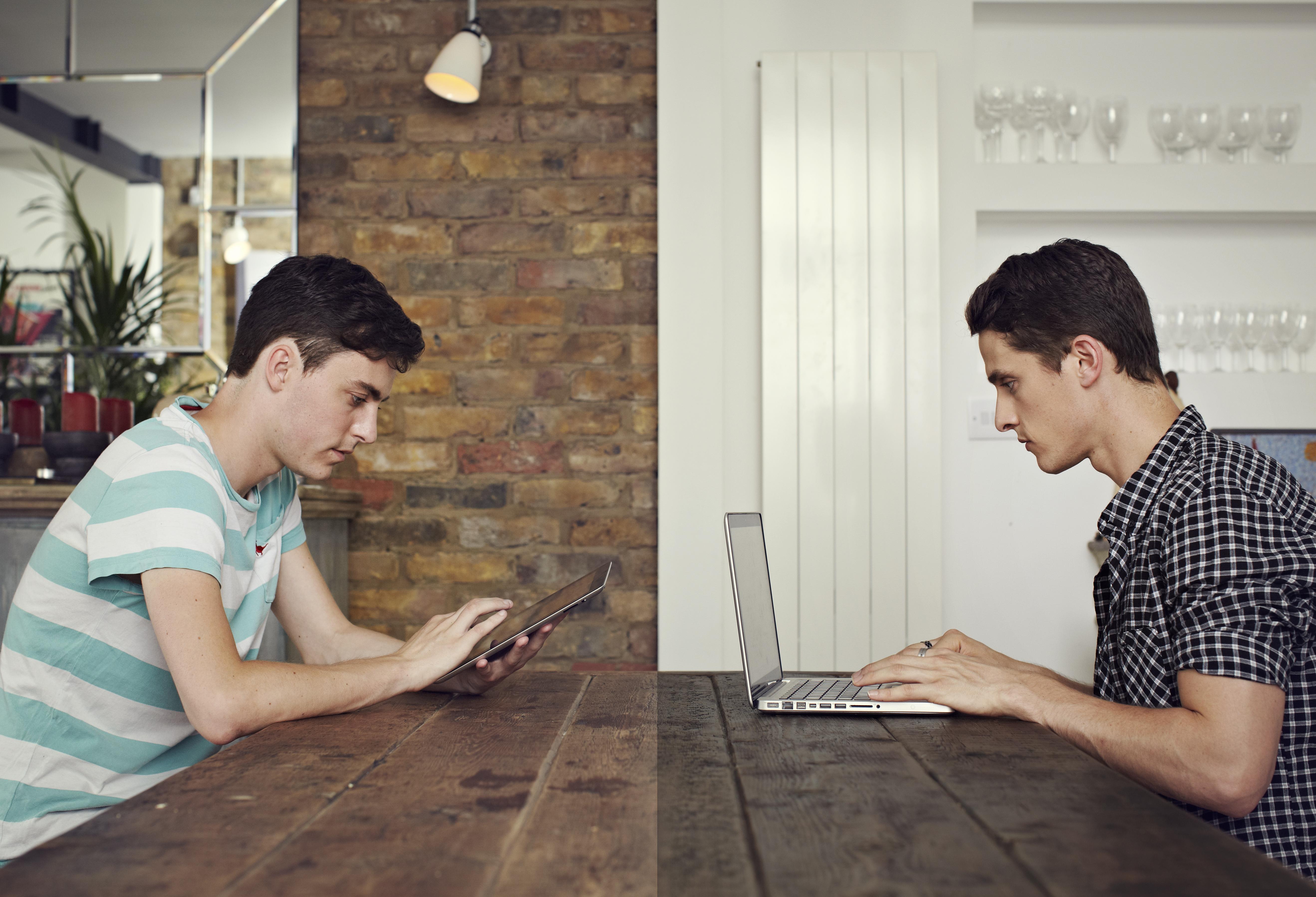 Men communicating through computers