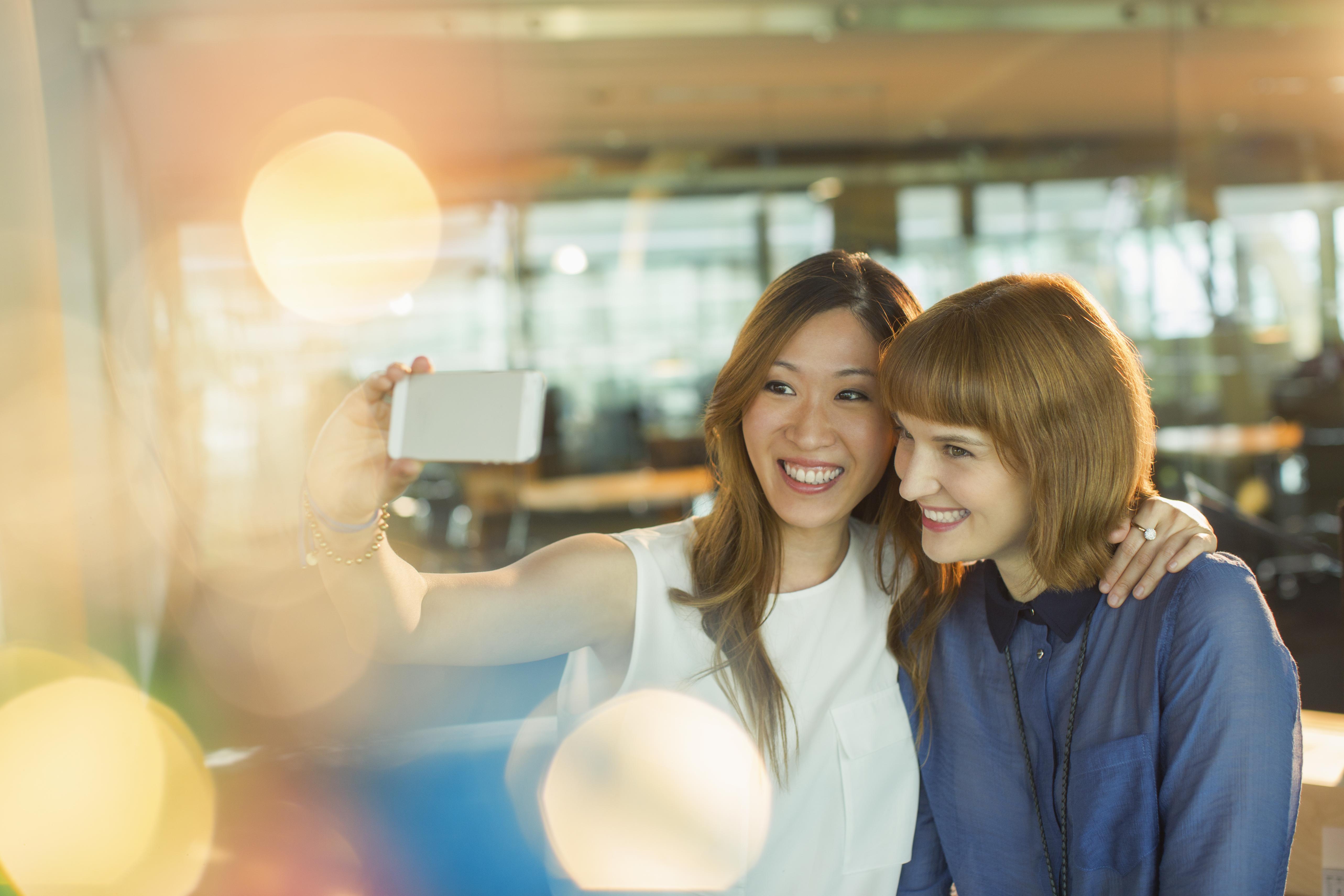 Businesswomen taking selfie in office