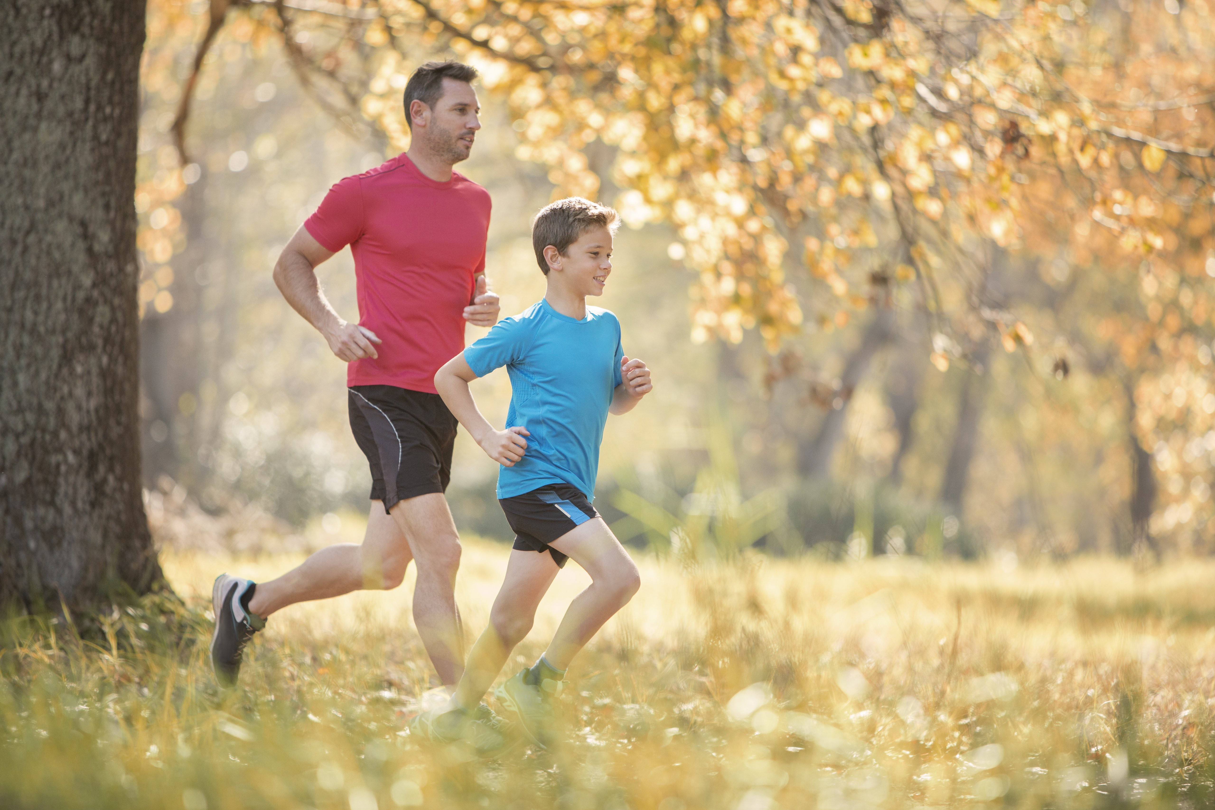 Father and son jogging in autumn park