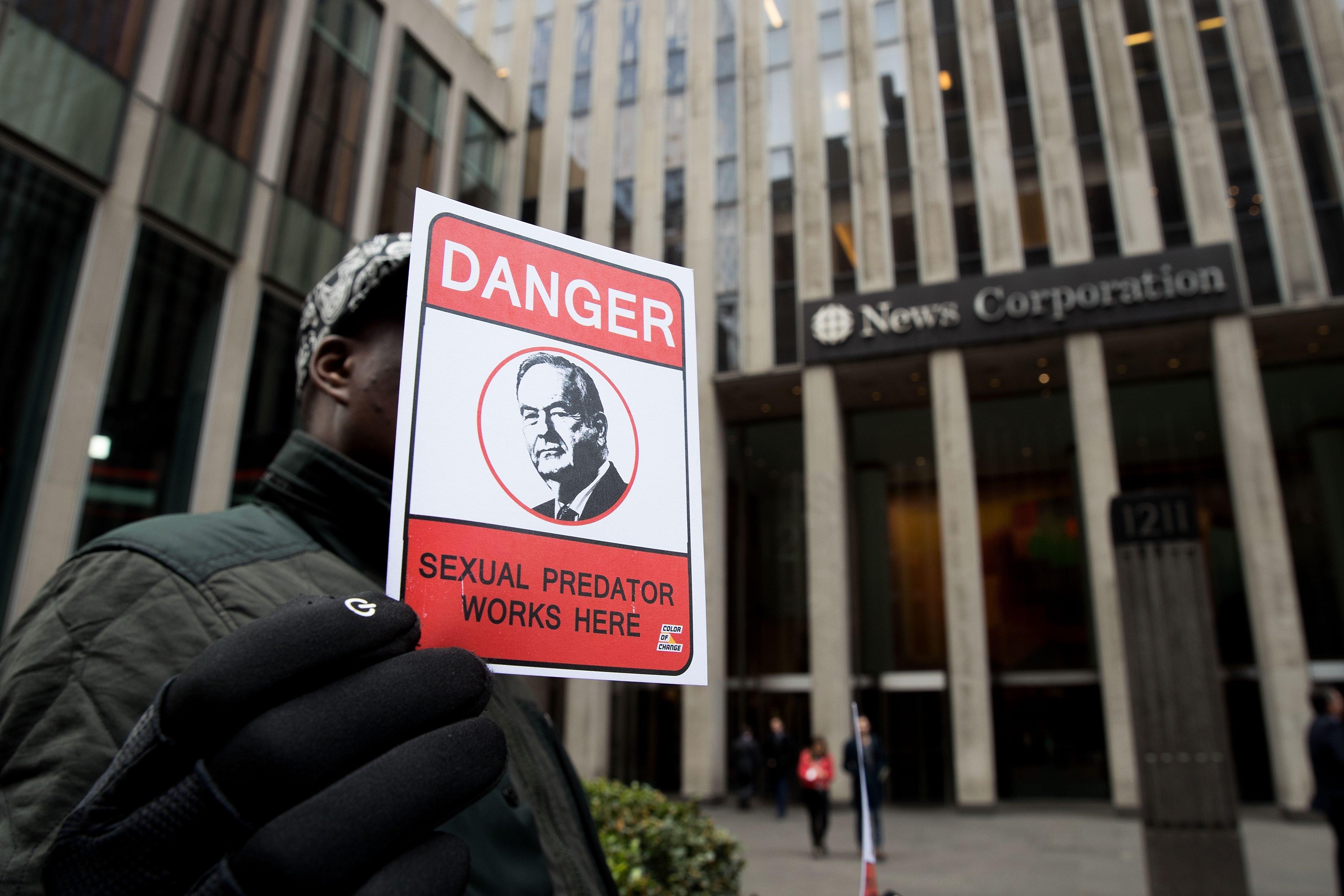 Demonstrator Matt Mitchell holds a sign outside of the News Corp. and Fox News headquarters in Midtown Manhattan, April 19, 2017 in New York City.