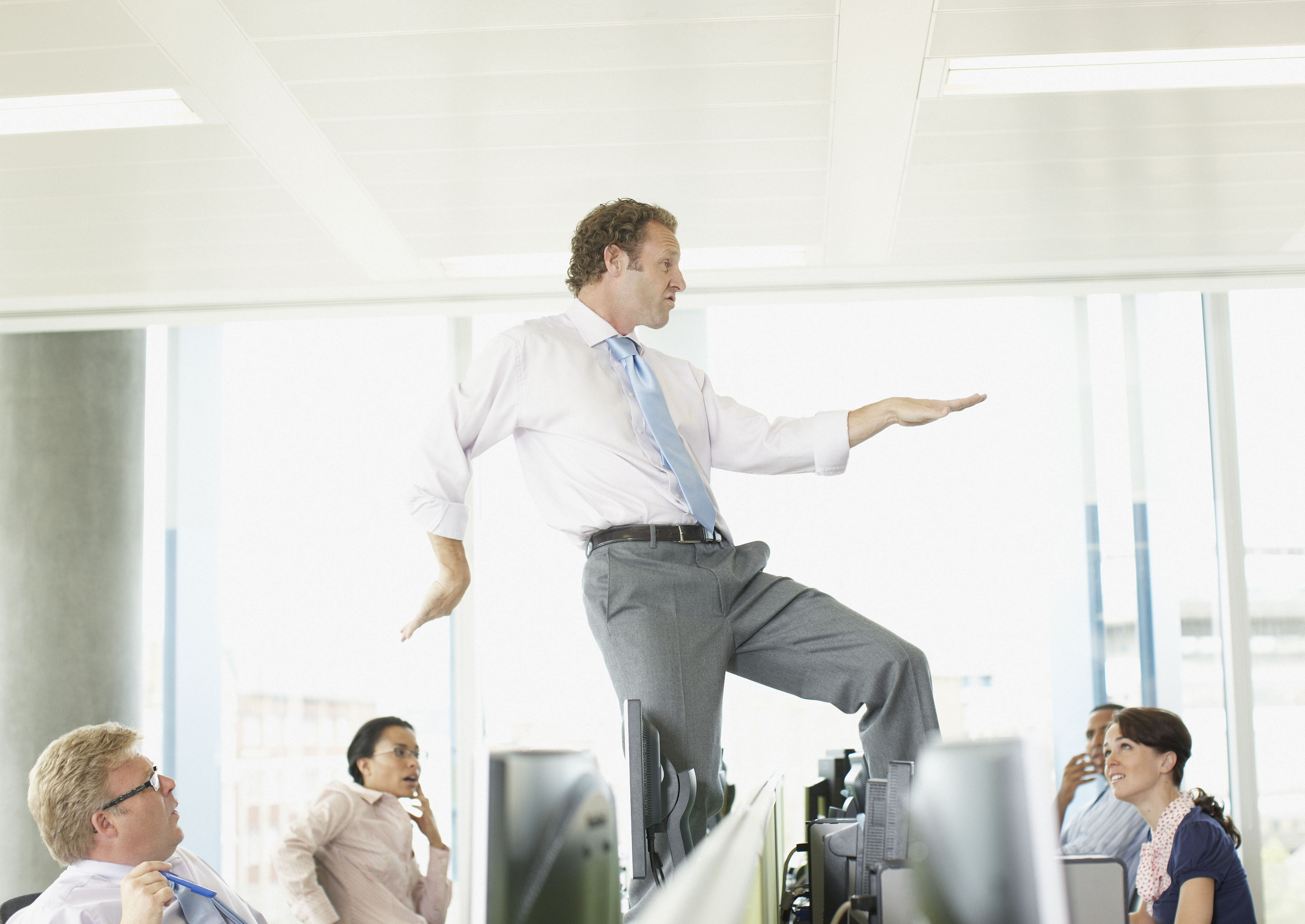 Businessman dancing on cubicle desk