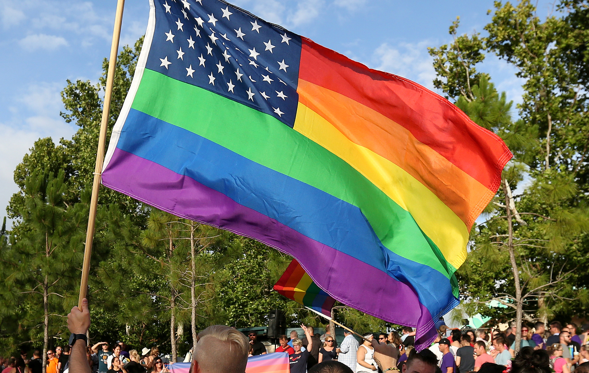 FILE PHOTO - A rainbow U.S. flag is held up during a vigil for the Pulse night club victims in Orlando