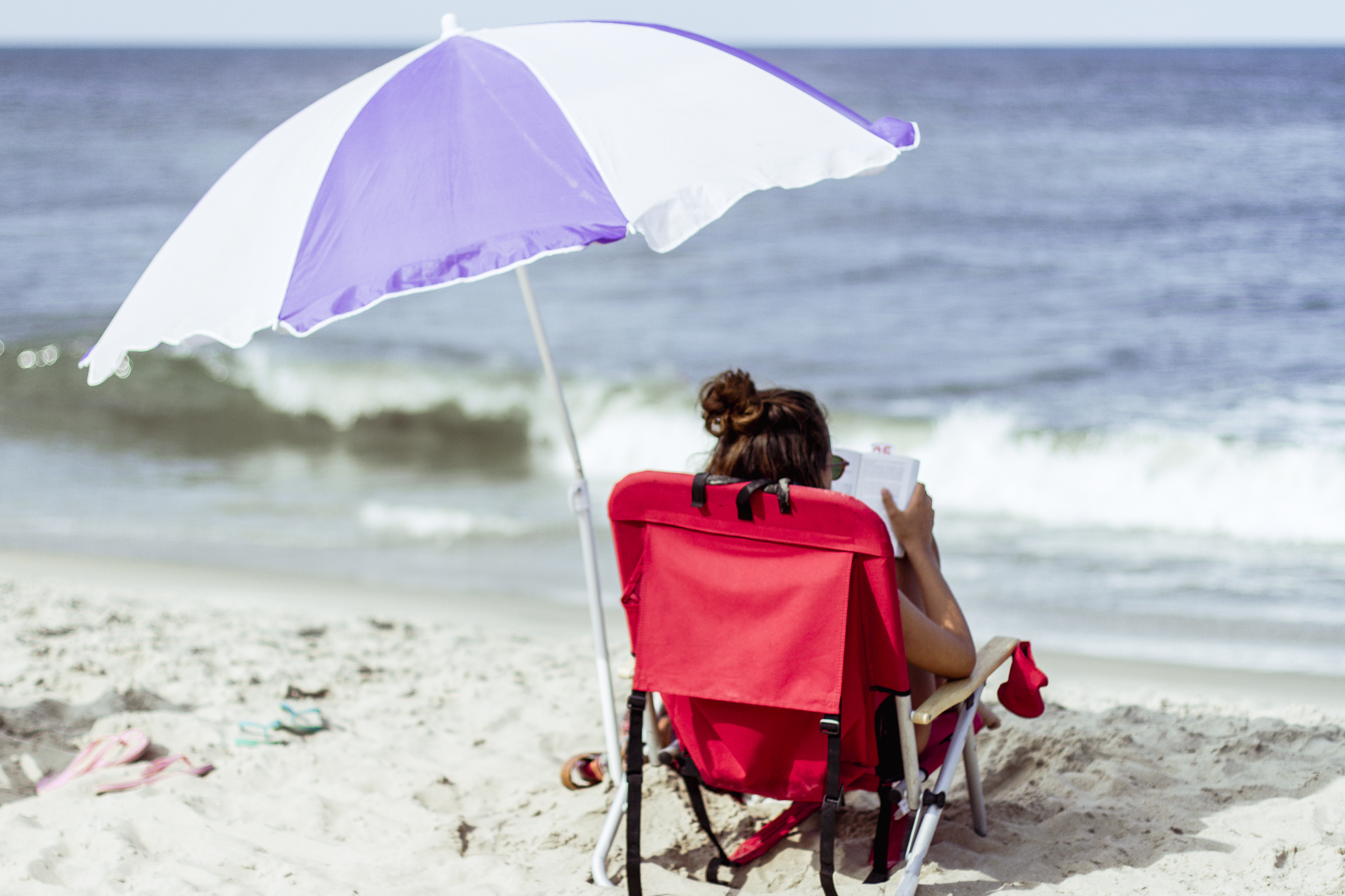 A girl reading on the beach and sitting on a red beach chair with a parasol