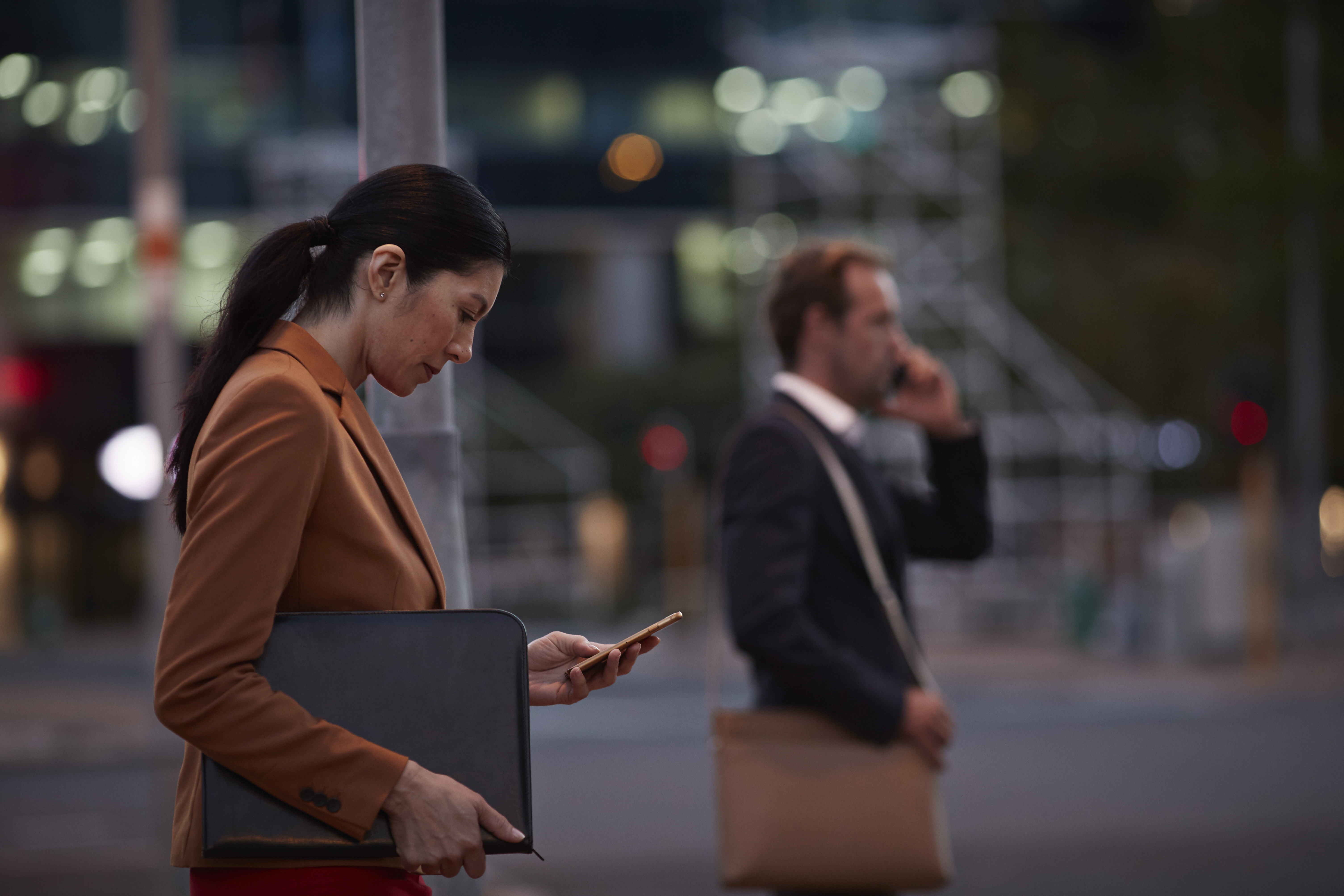 Businesswoman on street looking at phone, at night
