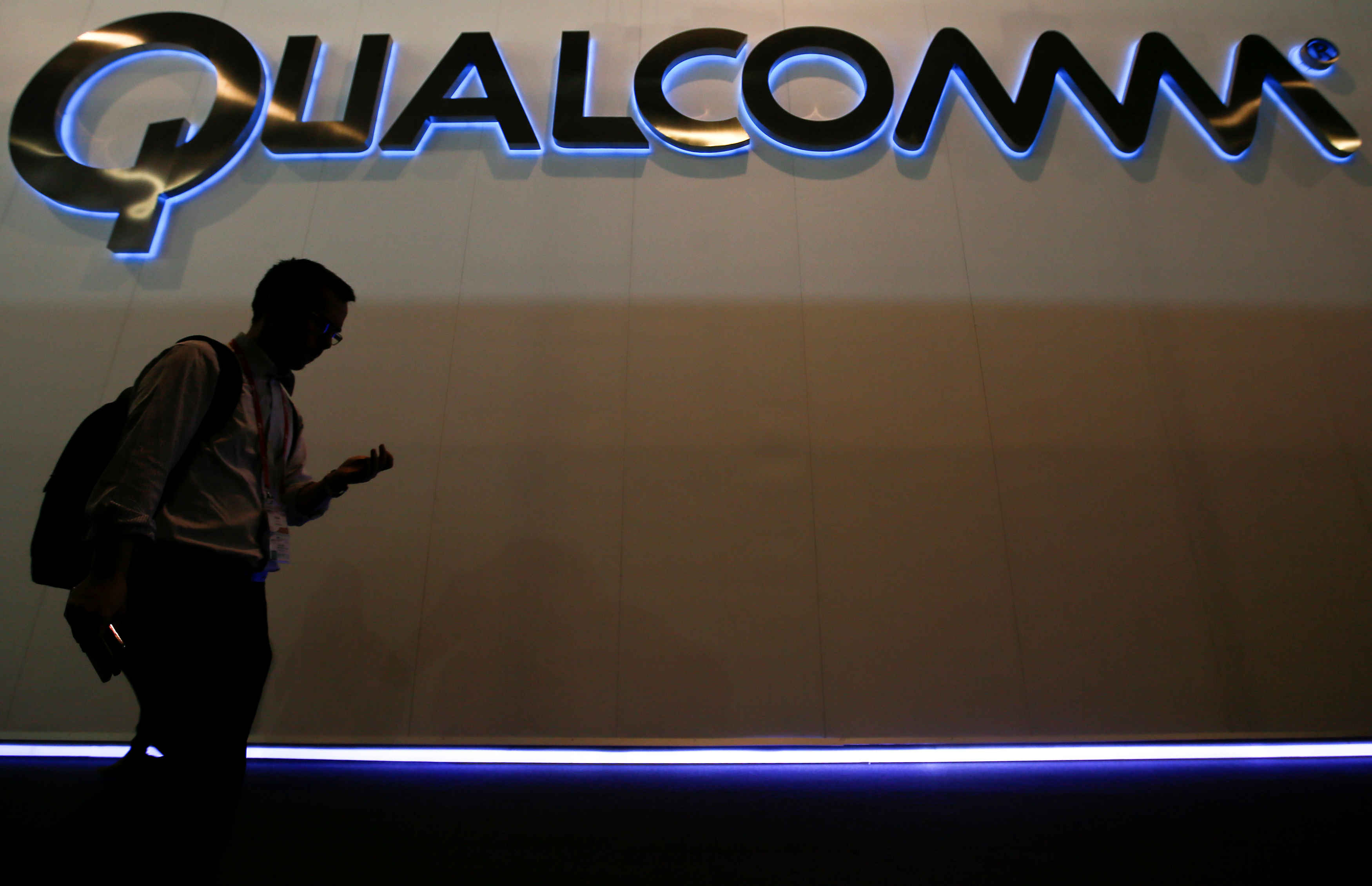 A man walks past Qualcomm stand while attending during the Mobile World Congress in Barcelona