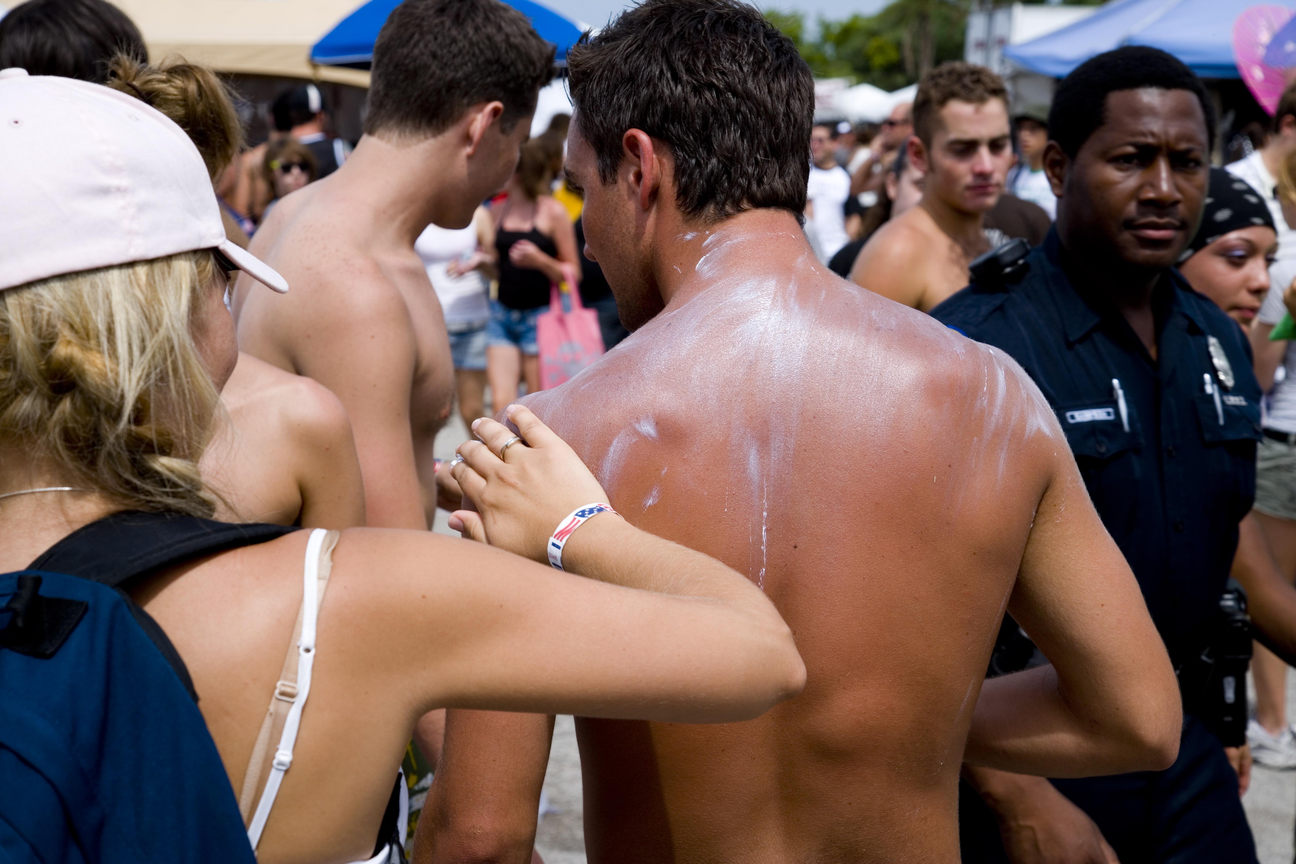 A girl applying suntan cream to the back of a sunburnt man. Vans Warped Tour, USA touring punk rock music festival, Bicentennial park, Miami, Florida, USA. 24th June 2006