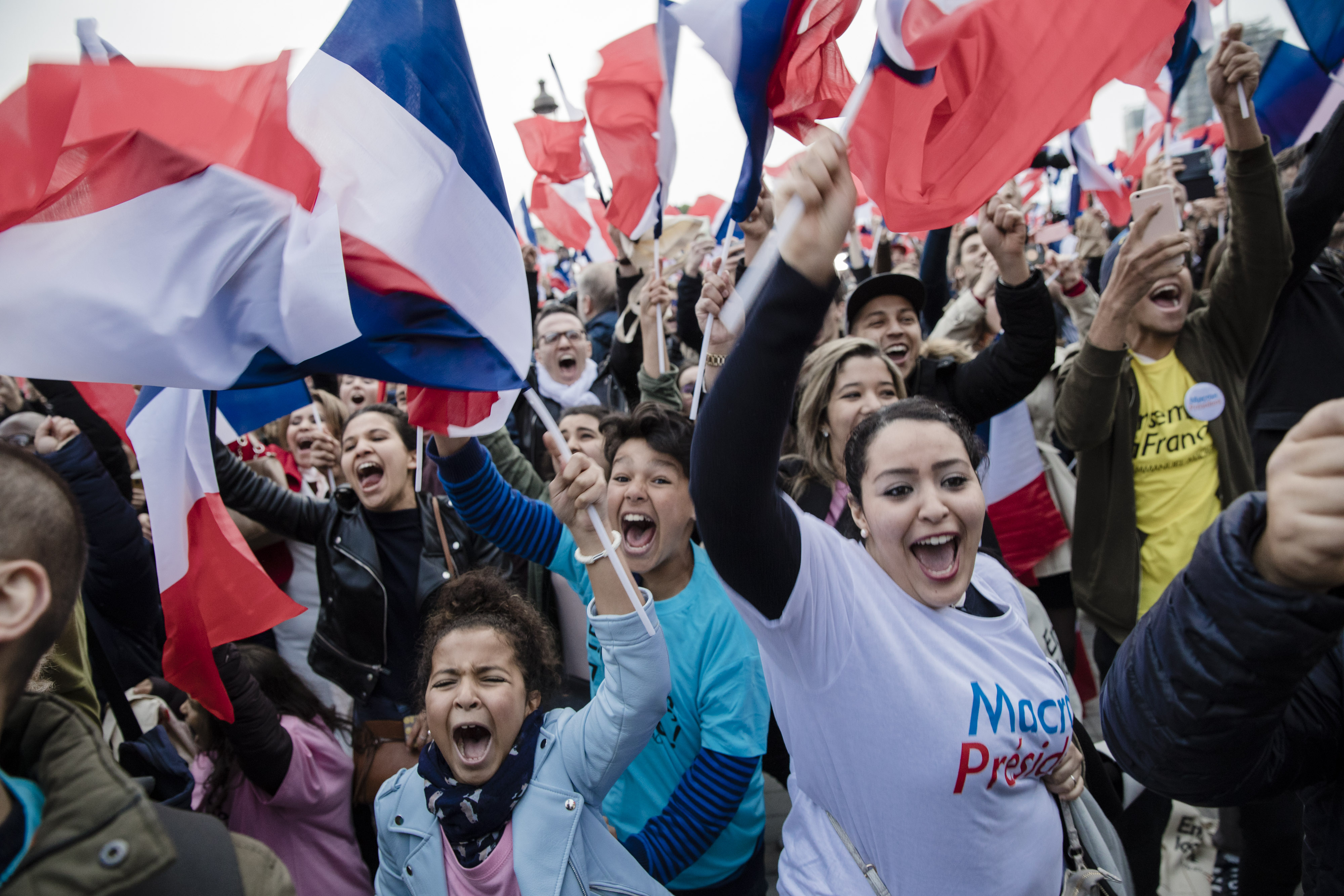 Supporters wave French national flags ahead of a speech by Emmanuel Macron, near the Louvre museum in Paris, on May 7, 2017.