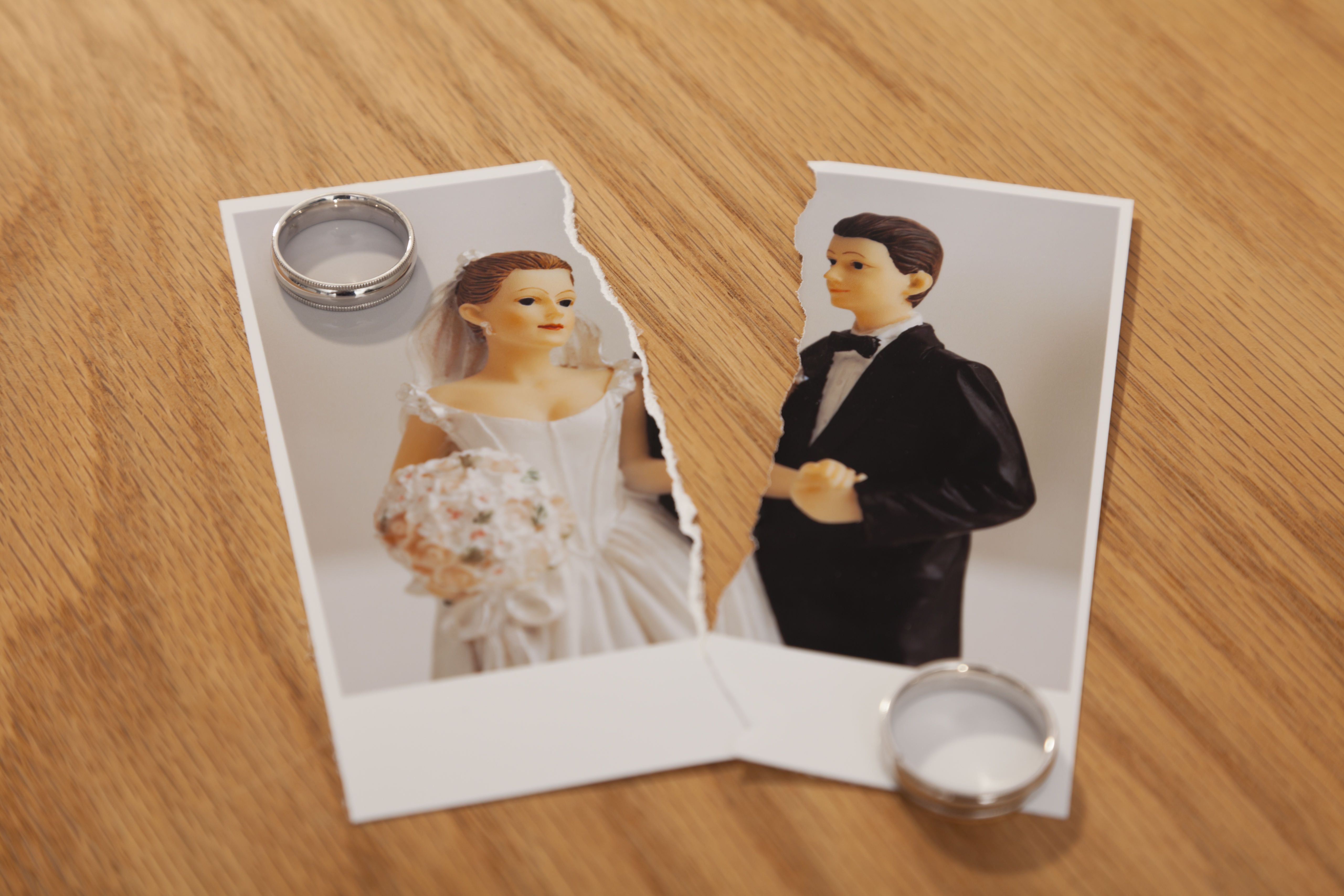 Studio shot of photo of bride and groom figurines torn in half and wedding rings