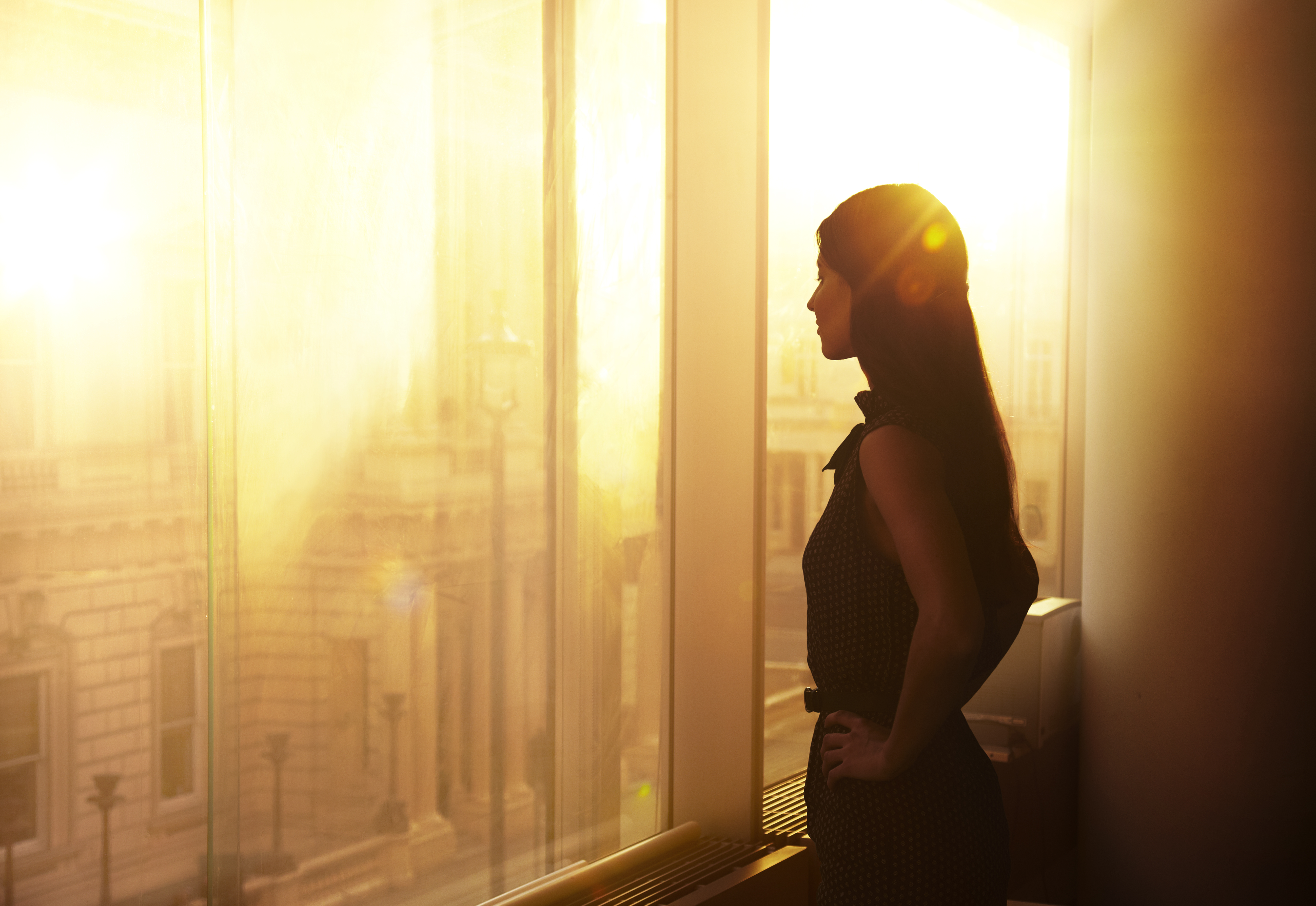 Businesswoman looking over the city at sunrise