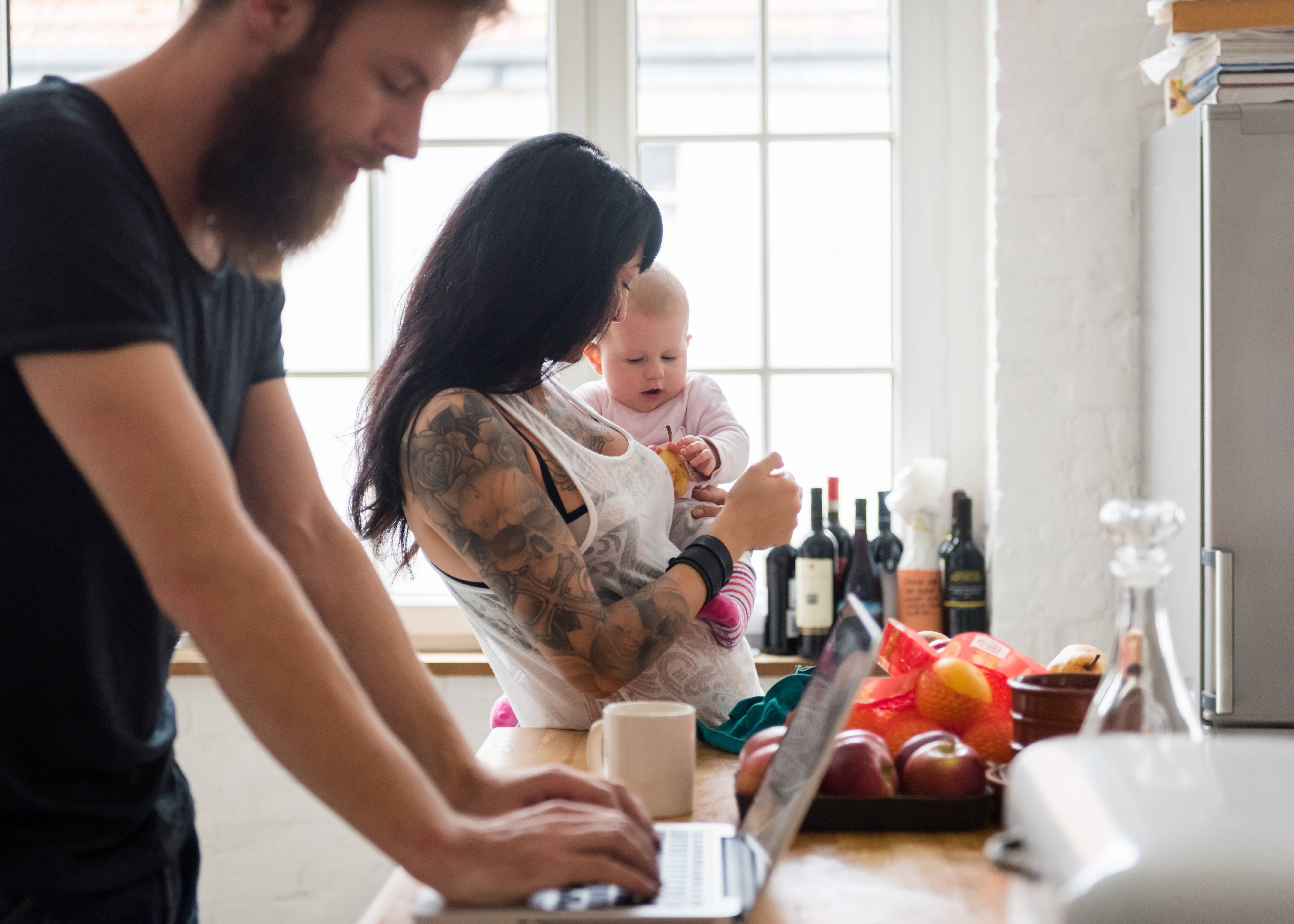 Young Family With Newborn Baby In Their Kitchen