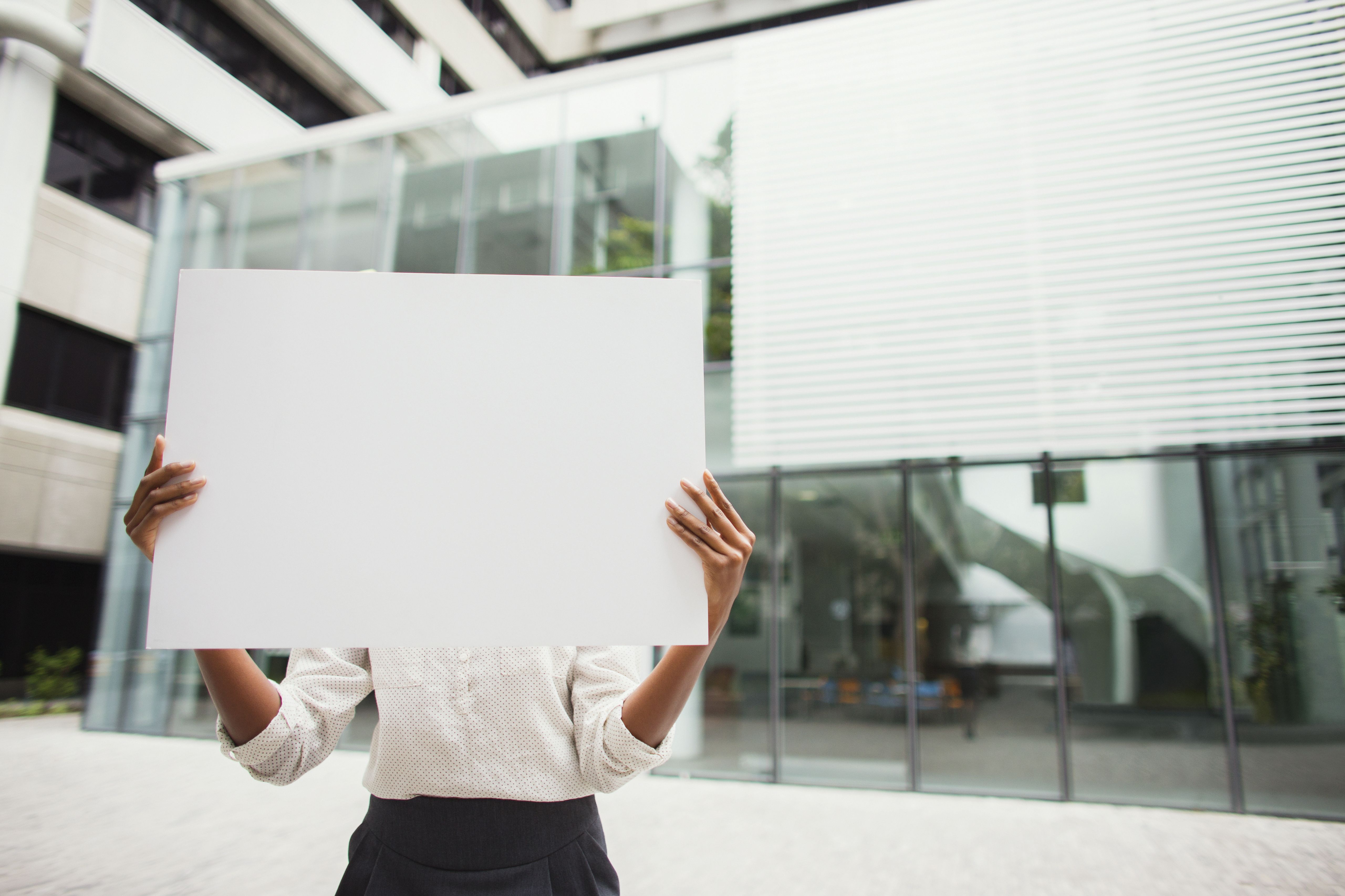 Businesswoman holding cardboard outside of office building