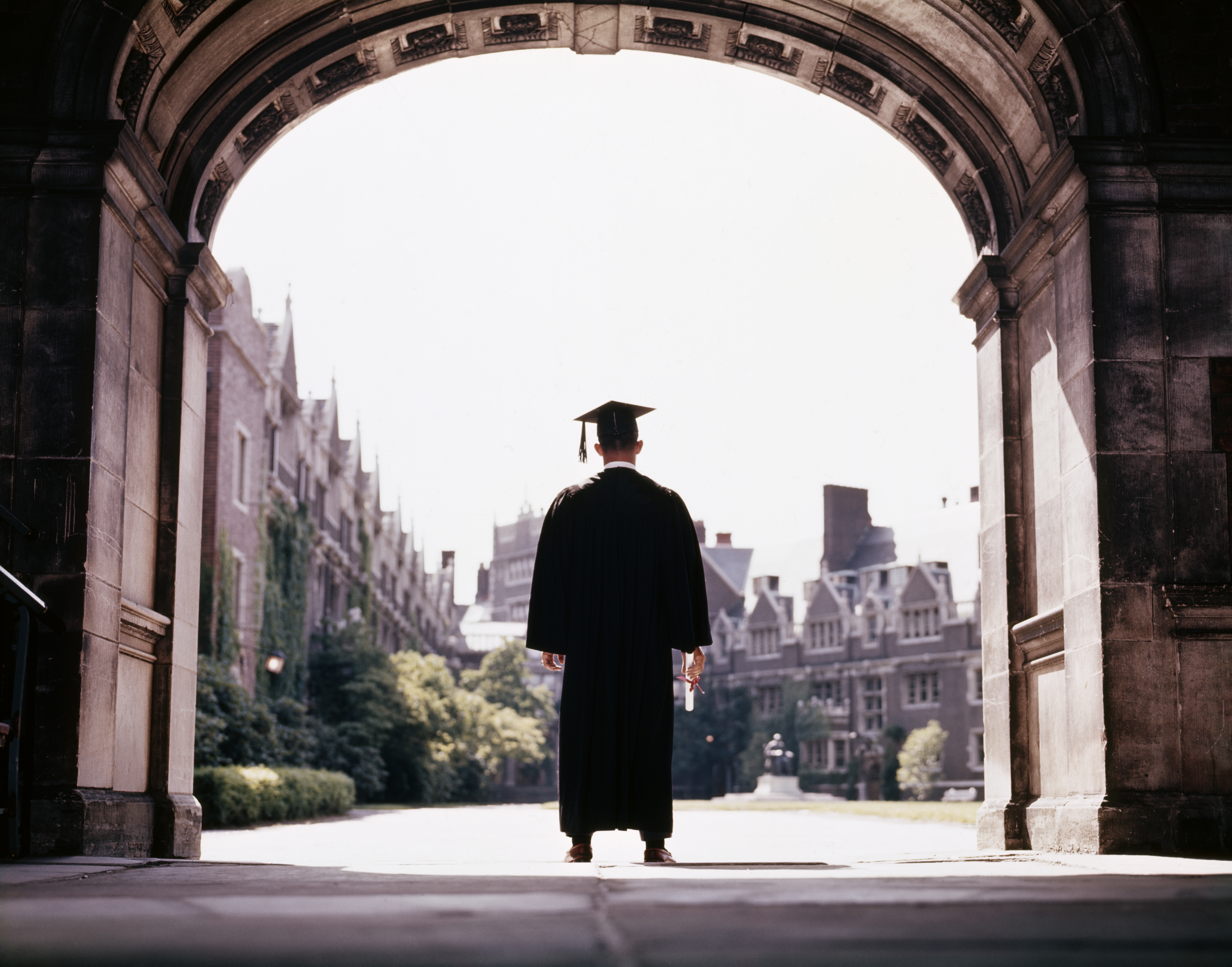 Male graduate wearing cap and gown standing in campus archway at University of Pennsylvania.