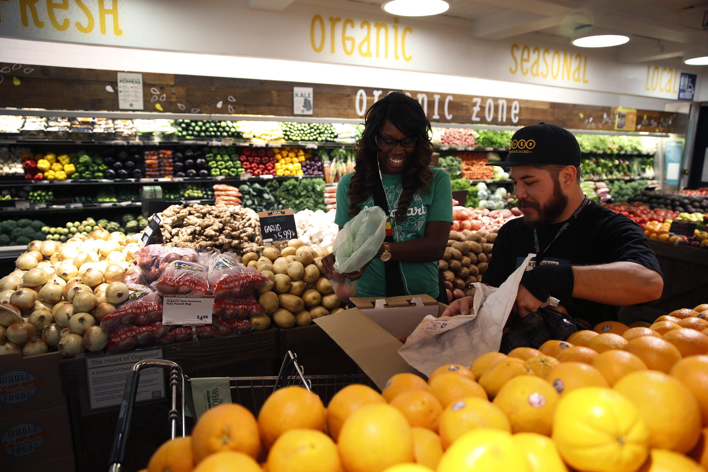 Whole Foods team member Matthew Otsuka opens a box of peaches for Instacart shopper Kara Pete as she shops for Concologist Tricia Carr.