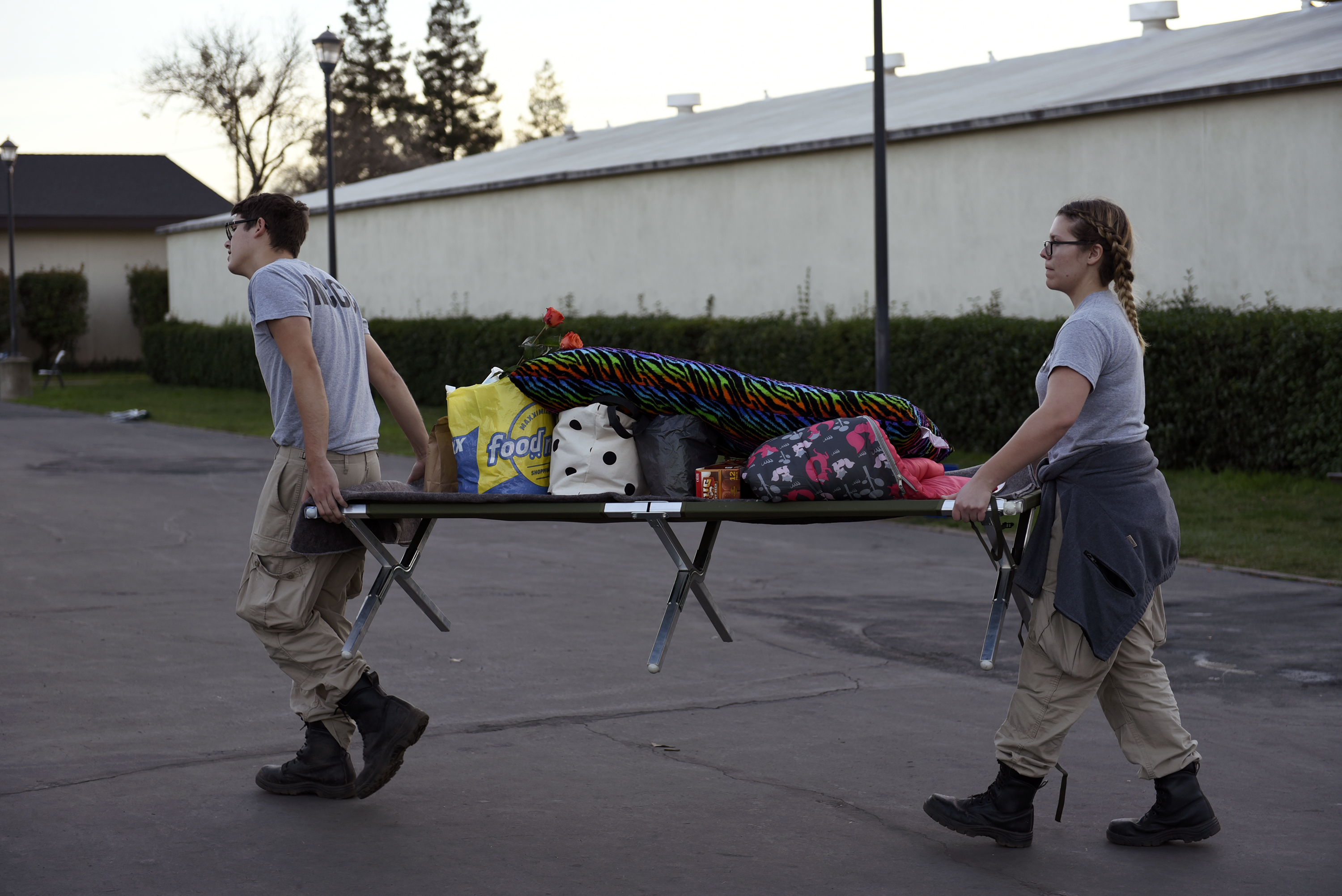 AmeriCorps volunteers carry a cot with donated items at the Silver Dollar Fairgrounds evacuation center in Chico, California, U.S., on Tuesday, Feb. 14, 2017. State officials rushed to repair an emergency spillway for the Oroville dam -- just 150 miles (241 kilometers) north of San Francisco -- that is threatening to submerge an entire region of northern California after a recent deluge of rain.
