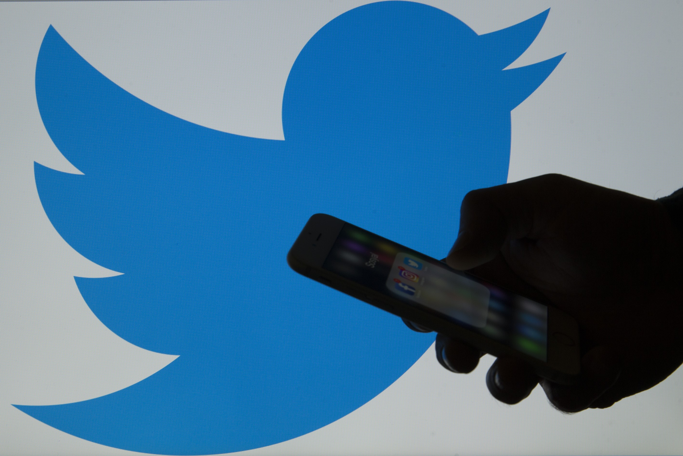 A picture shows a man holding a cellphone in front of a twitter logo in Ankara, Turkey on March 16, 2017